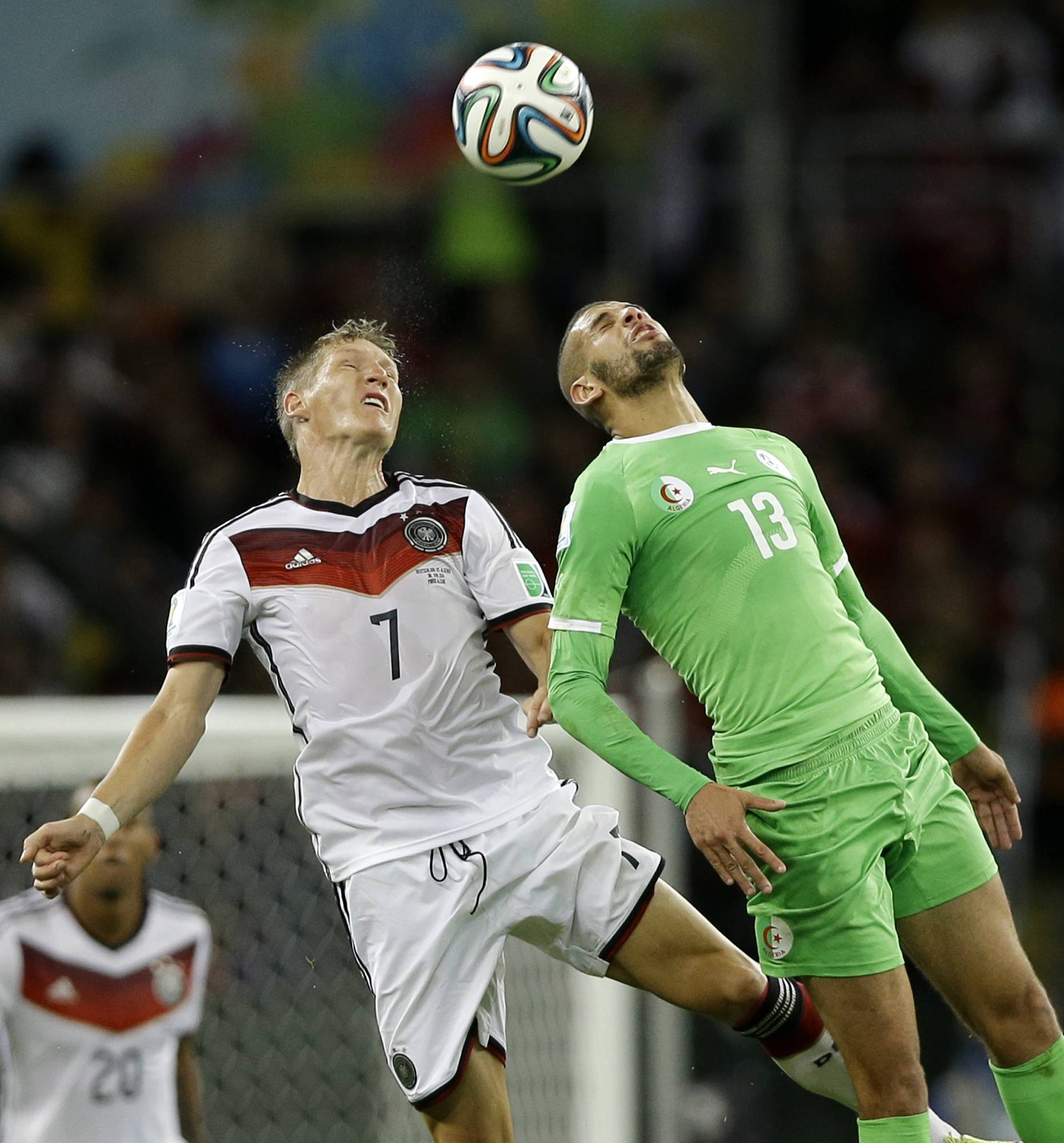 Germany's Bastian Schweinsteiger, left, heads the ball against Algeria's Islam Slimani during the World Cup round of 16 soccer match between Germany and Algeria at the Estadio Beira-Rio in Porto Alegre, Brazil, Monday, June 30, 2014.