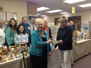 Rosemary Argus presents Debbie Walusiak of the Self Help Pantry and Closet with a $5,000 donation. Volunteers at the pantry are in the background.