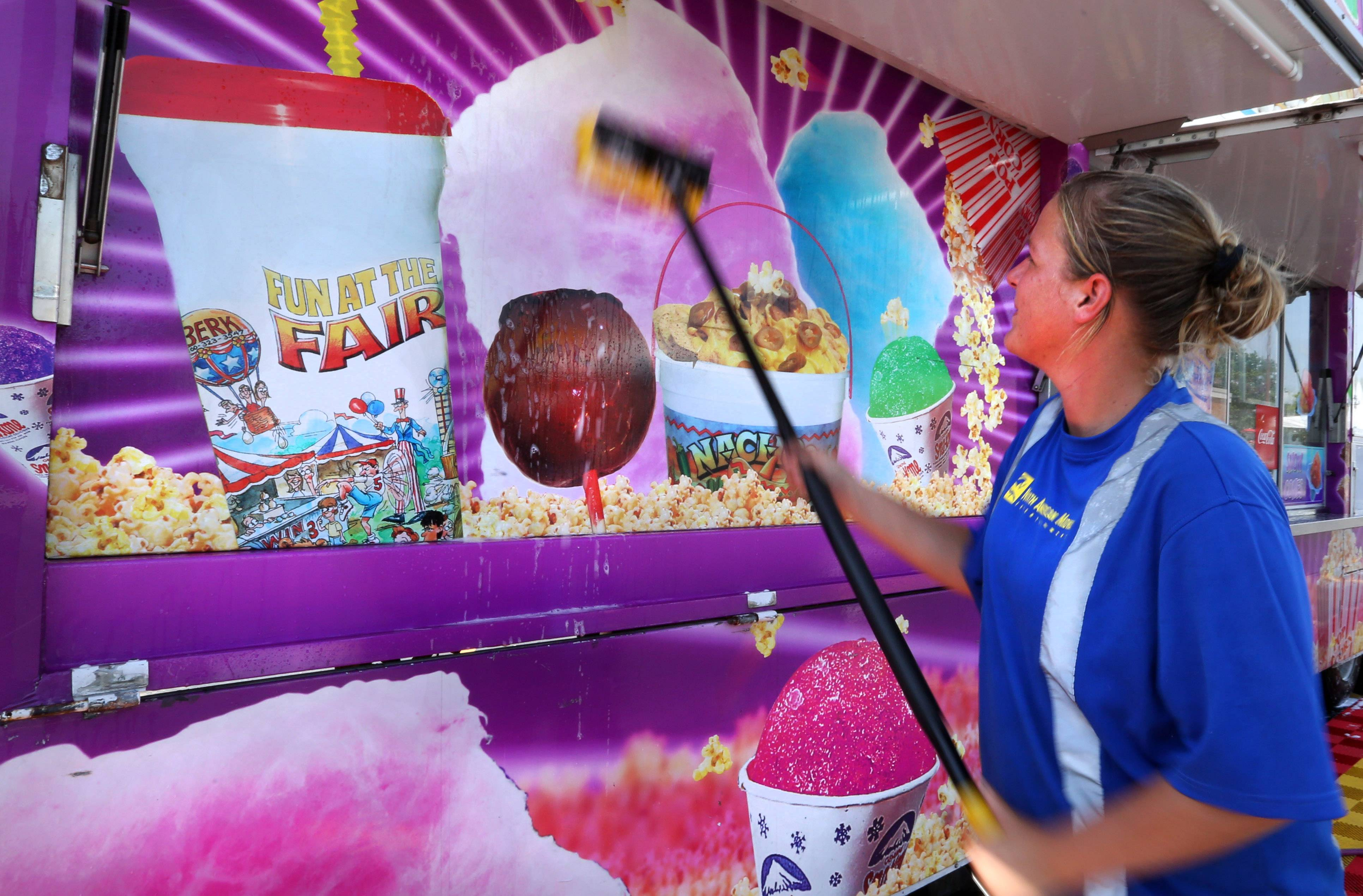 Christina Blanton, of Florida scrubs down the exterior of Sugar Babies Treats, getting it ready for Wednesday's Frontier Days opening.