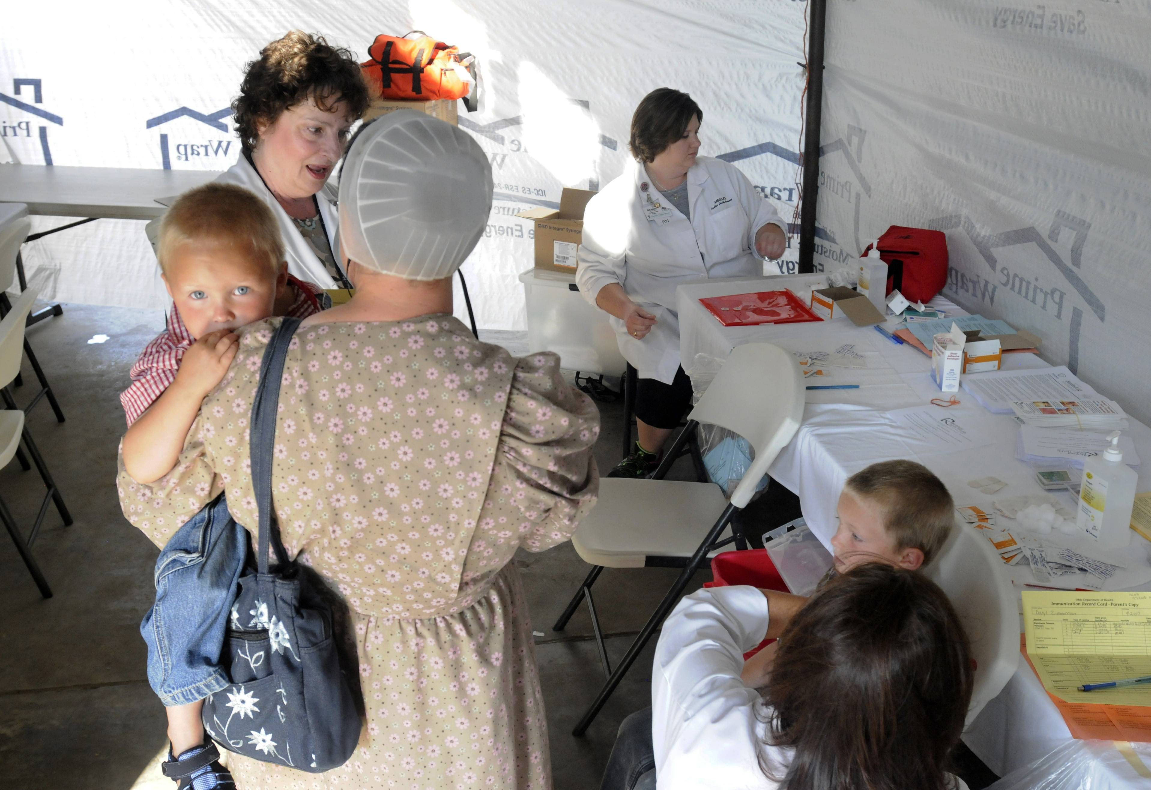 Richland Public Health nurse Sue McFarren talks with a Mennonite mother and child at a Measles, Mumps, & Rubella (MMR) clinic for the Mennonite community in Richland County in Shiloh, Ohio.