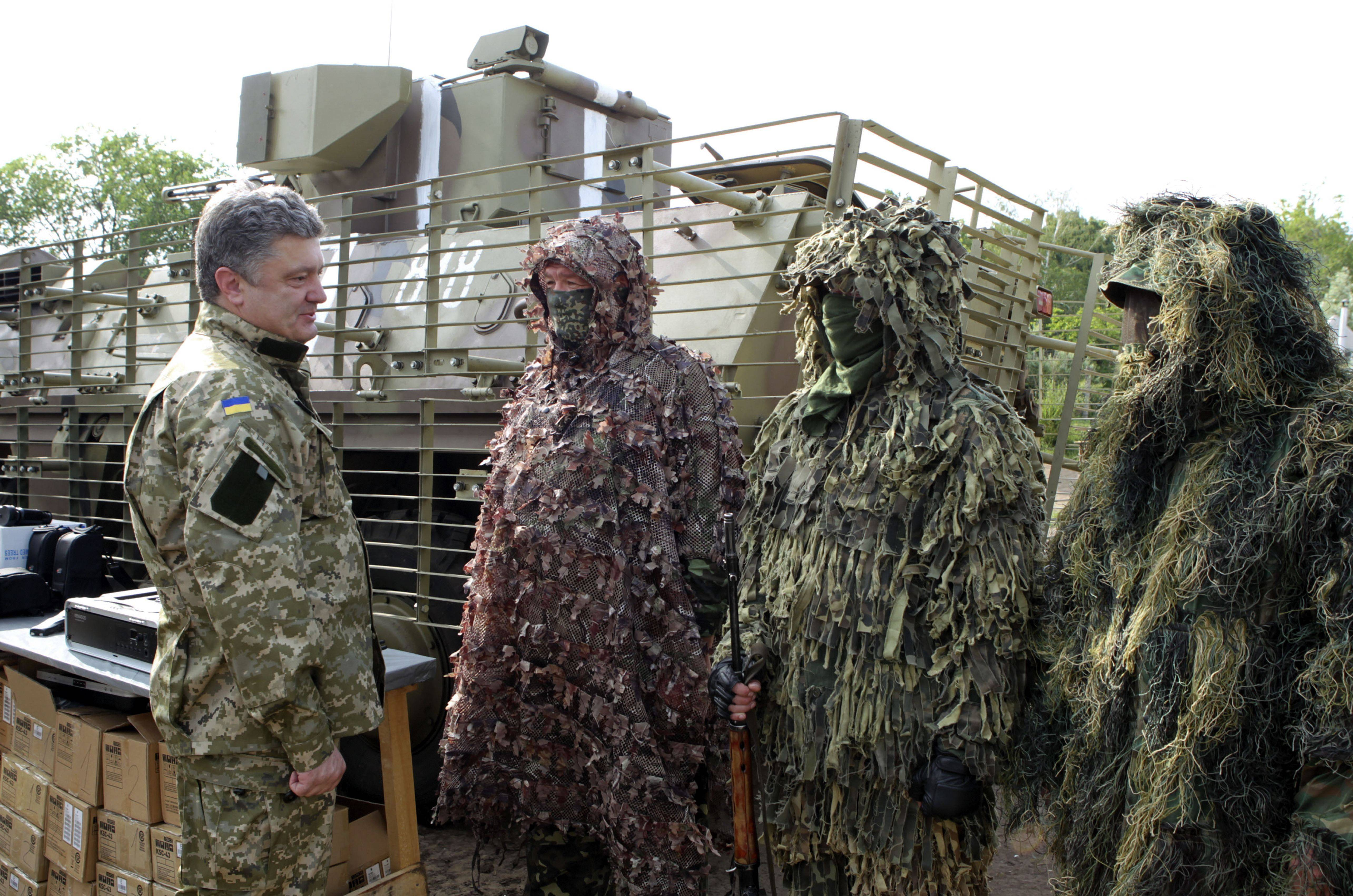 In this photo taken on Friday, eastern Ukraine Ukrainian President Petro Poroshenko, left, visits troops. Poroshenko in a televised address early Tuesday said he was abandoning a unilateral cease-fire in the conflict with pro-Russian separatists and sending military forces back on the offensive after talks with Russia and European leaders failed to start a broader peace process. The cease-fire expired Monday evening.