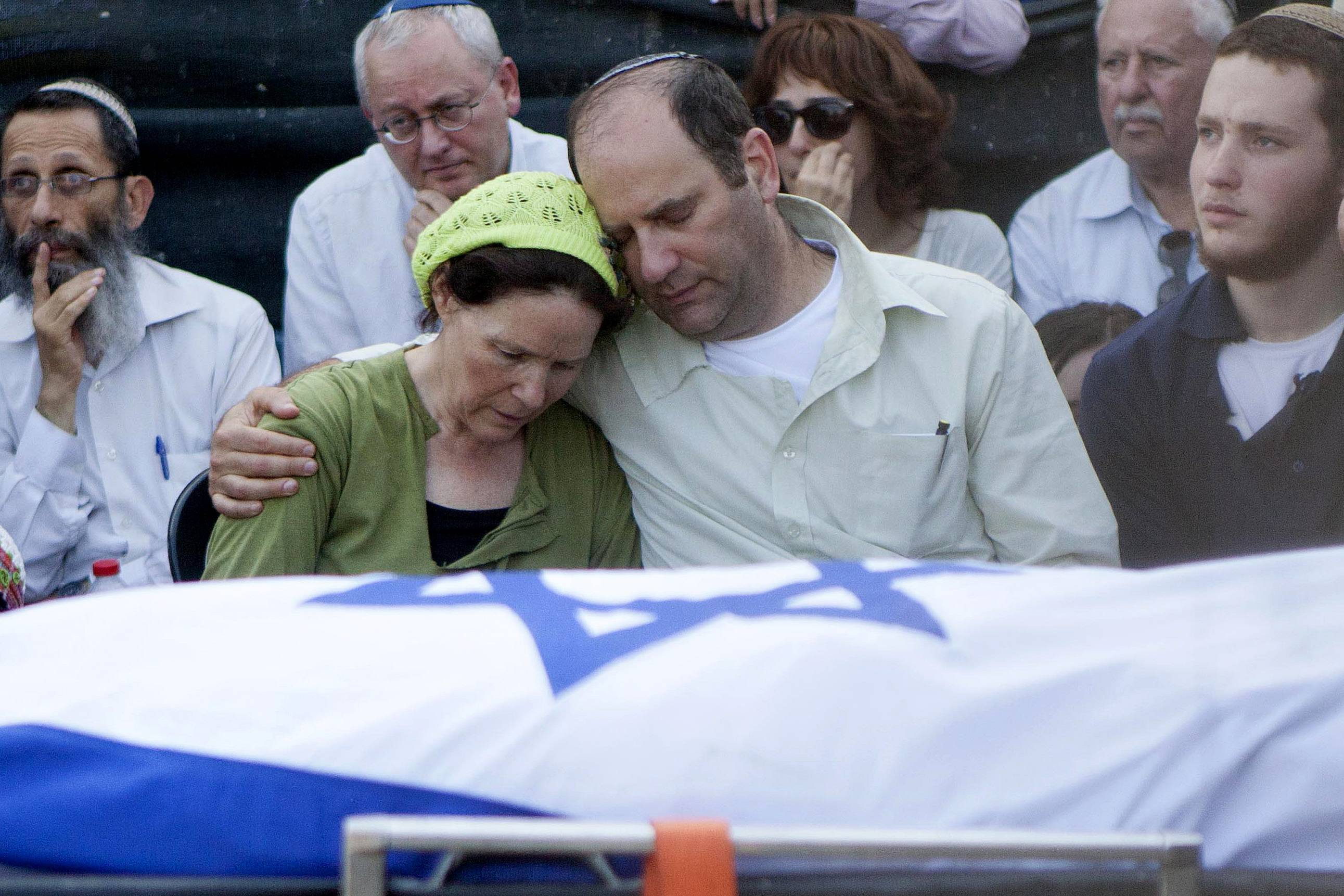 Avi and Rachel Fraenkel embrace during the funeral of their son, Naftali, a 16-year-old with dual Israeli-American citizenship, in the West Bank Jewish settlement of Nof Ayalon on Tuesday.