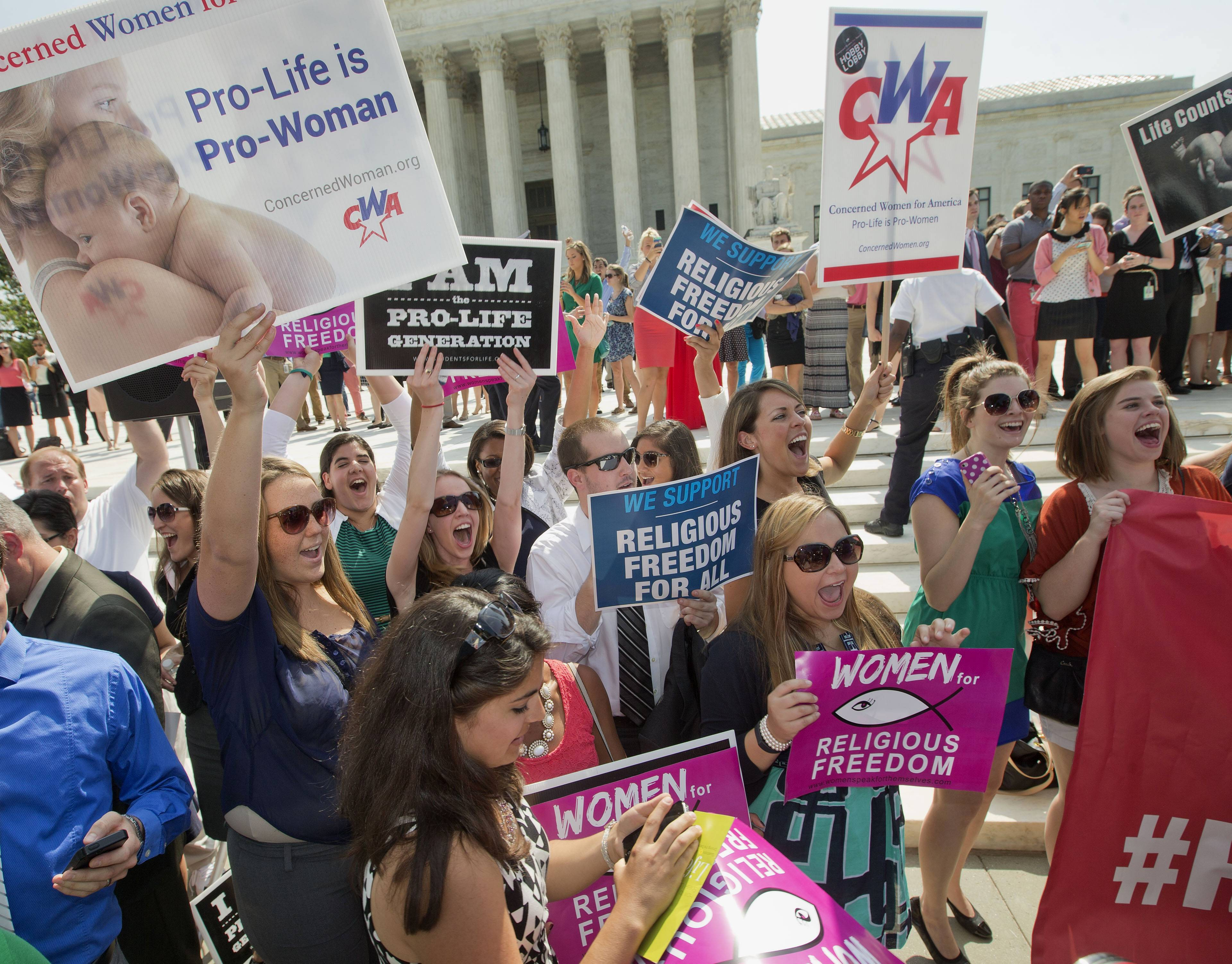 Demonstrator react to hearing the Supreme Court's decision on the Hobby Lobby case outside the Supreme Court on Monday, when the Supreme Court ruled corporations can hold religious objections that allow them to opt out of the new health law requirement that they cover contraceptives for women.