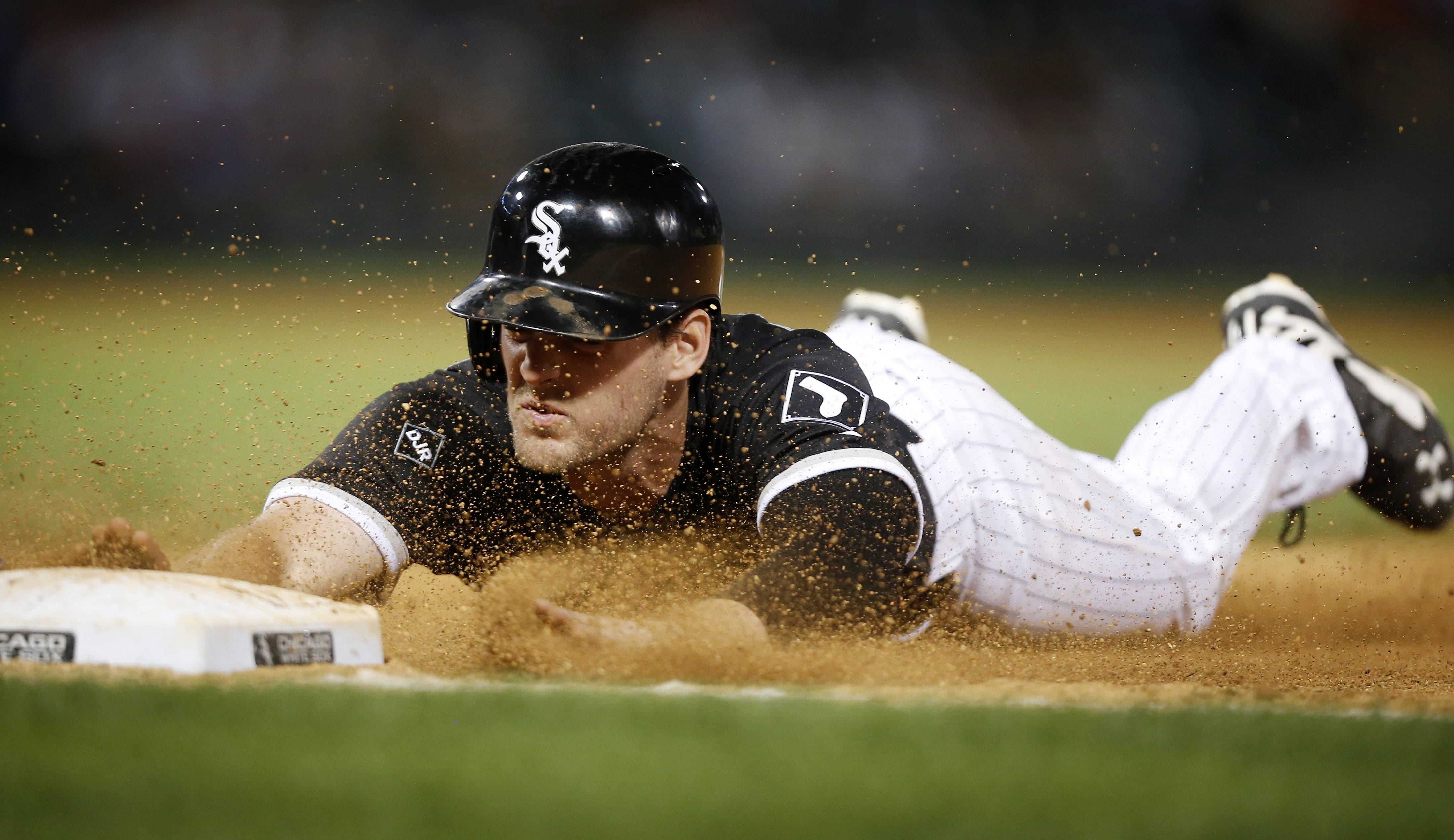 Chicago White Sox's Conor Gillaspie safely dives back to first after teammate Dayan Viciedo lined out against the Los Angeles Angels during the eighth inning of the second baseball game of a doubleheader on Tuesday, July 1, 2014, in Chicago.