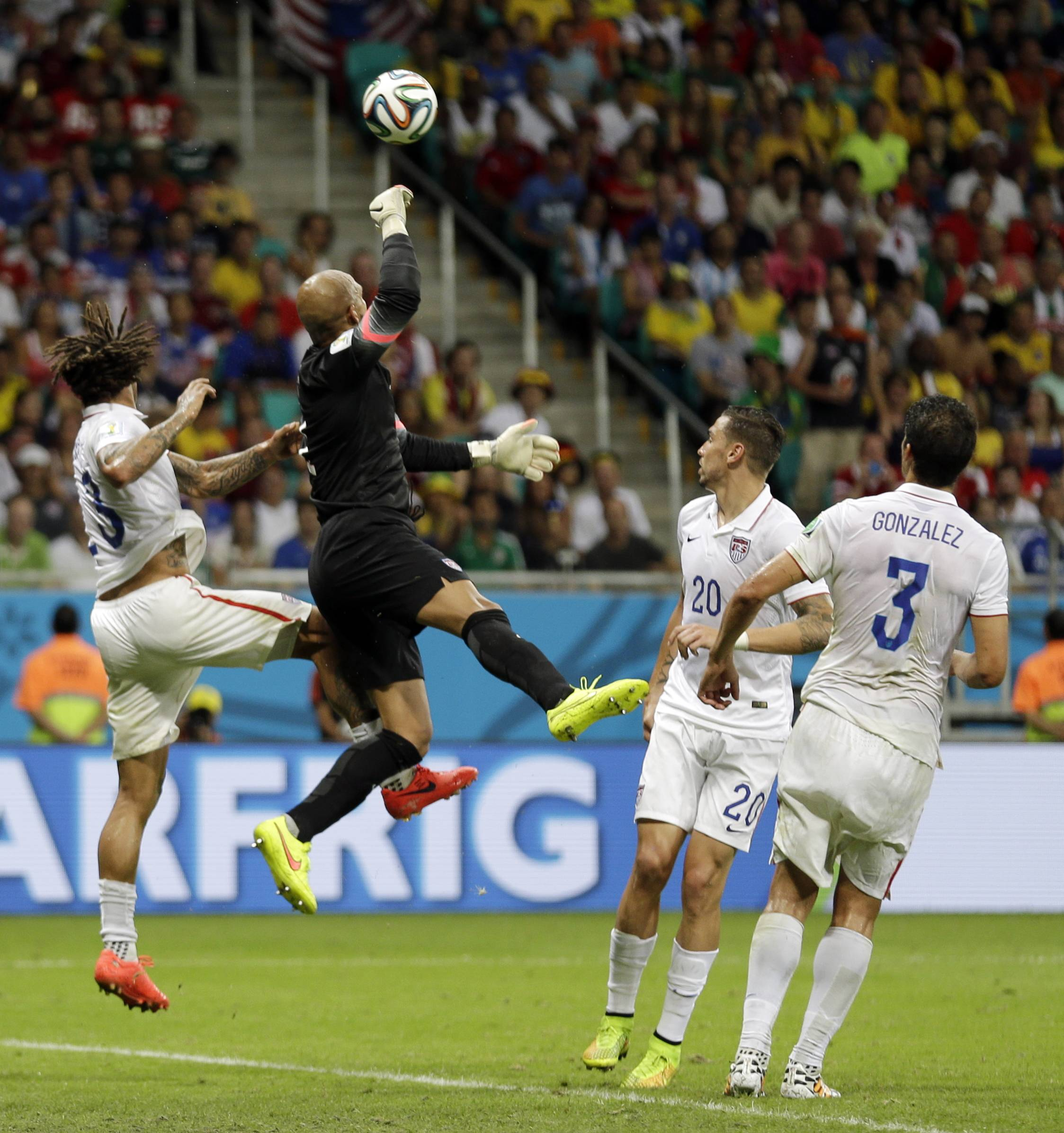 United States' goalkeeper Tim Howard leaps in between his teammates to clear the ball during the World Cup round of 16 soccer match between Belgium and the USA at the Arena Fonte Nova in Salvador, Brazil, Tuesday, July 1, 2014. (AP Photo/Natacha Pisarenko)