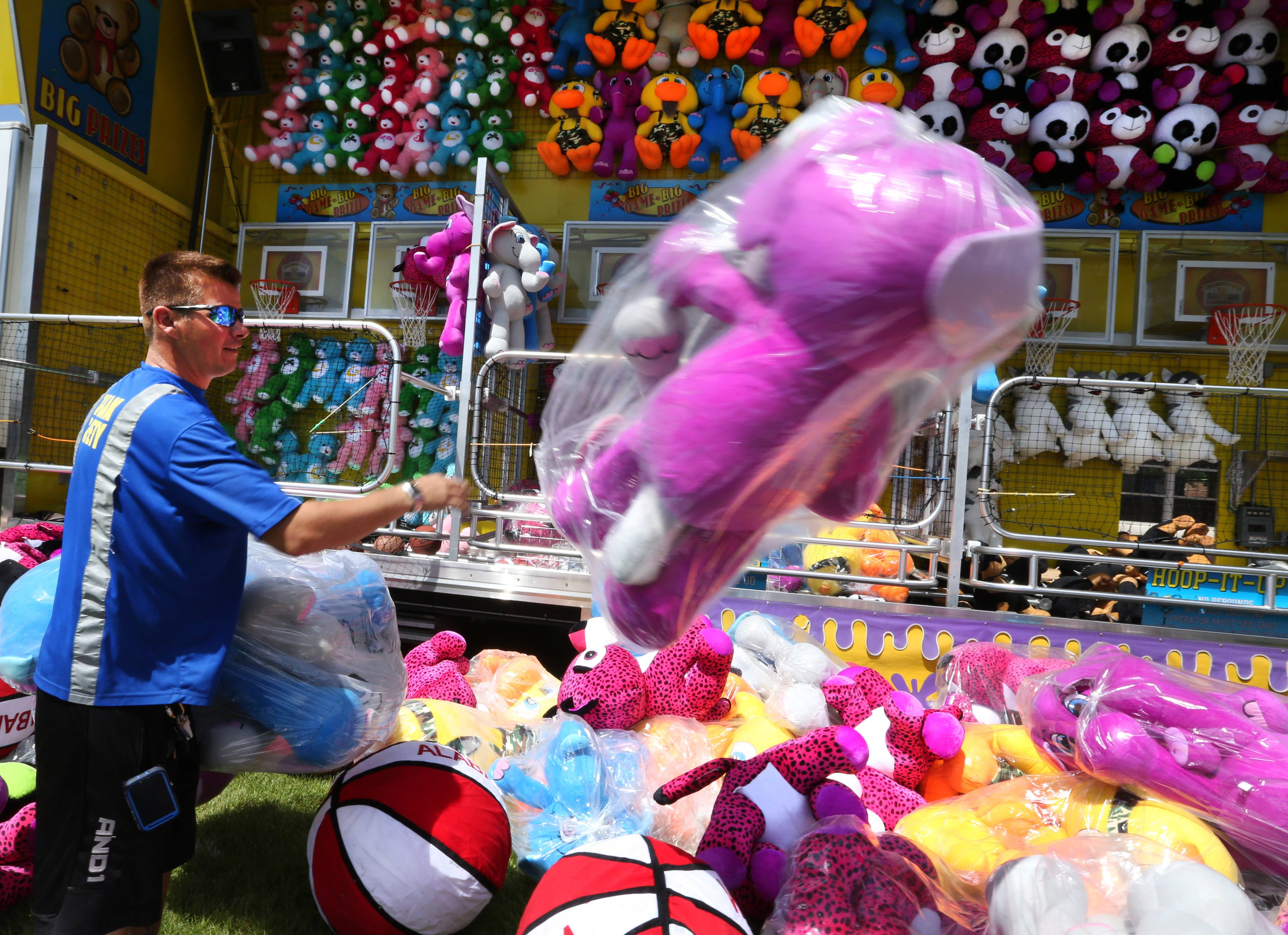 Daniel Mason, a carnival worker from Indiana, arranges his display of prizes outside the basketball game.