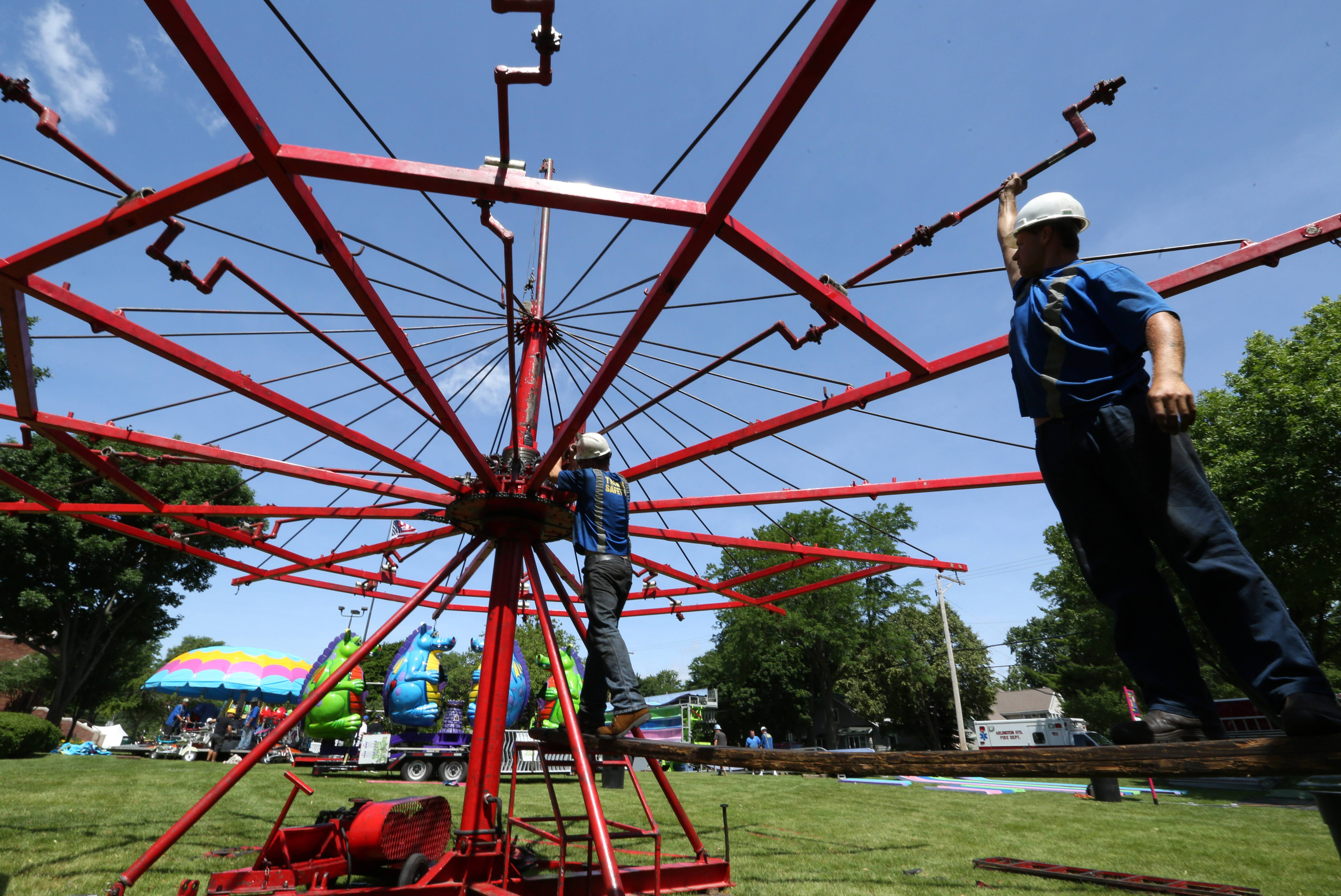 Workers assemble a ride at Recreation Park in Arlington Heights for Wednesday's opening.