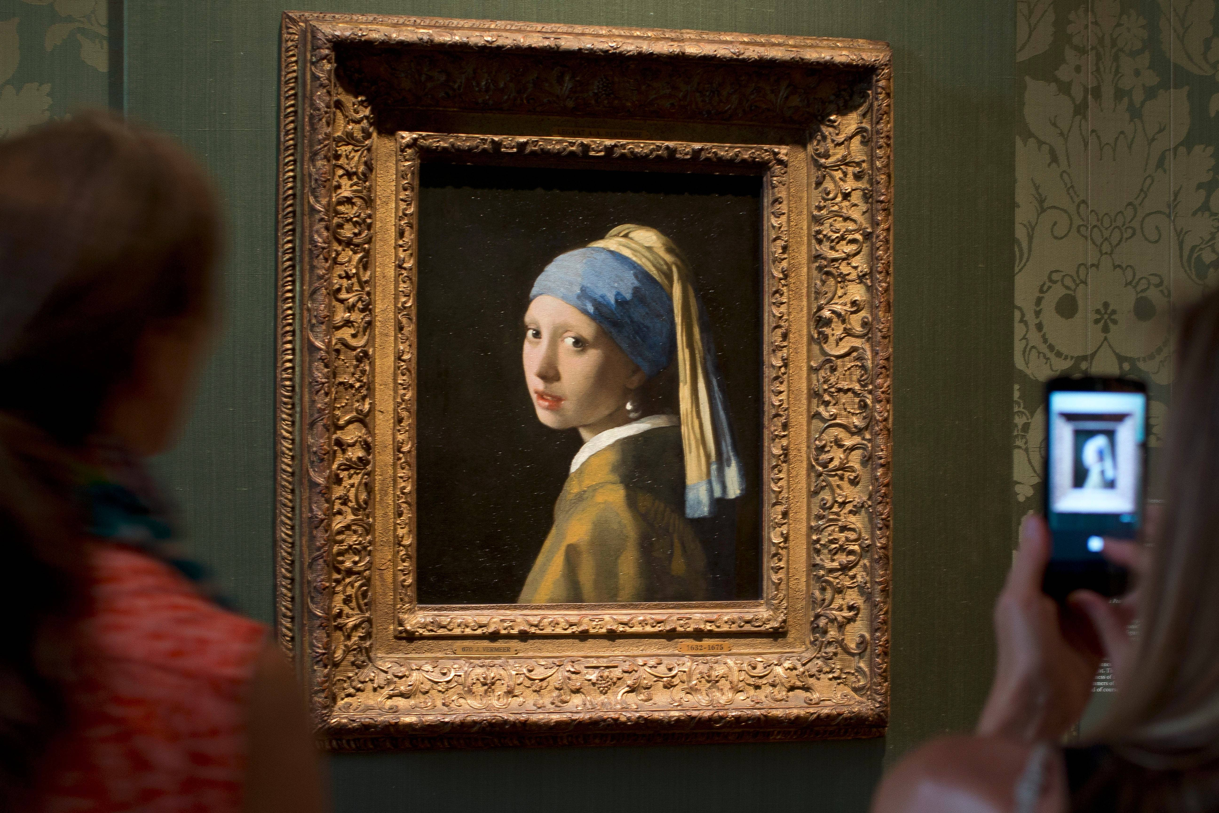 "Visitors take pictures of Johannes Vermeer's ""Girl with a Pearl Earring"" (approx. 1665) at the Mauritshuis in The Hague, Netherlands."