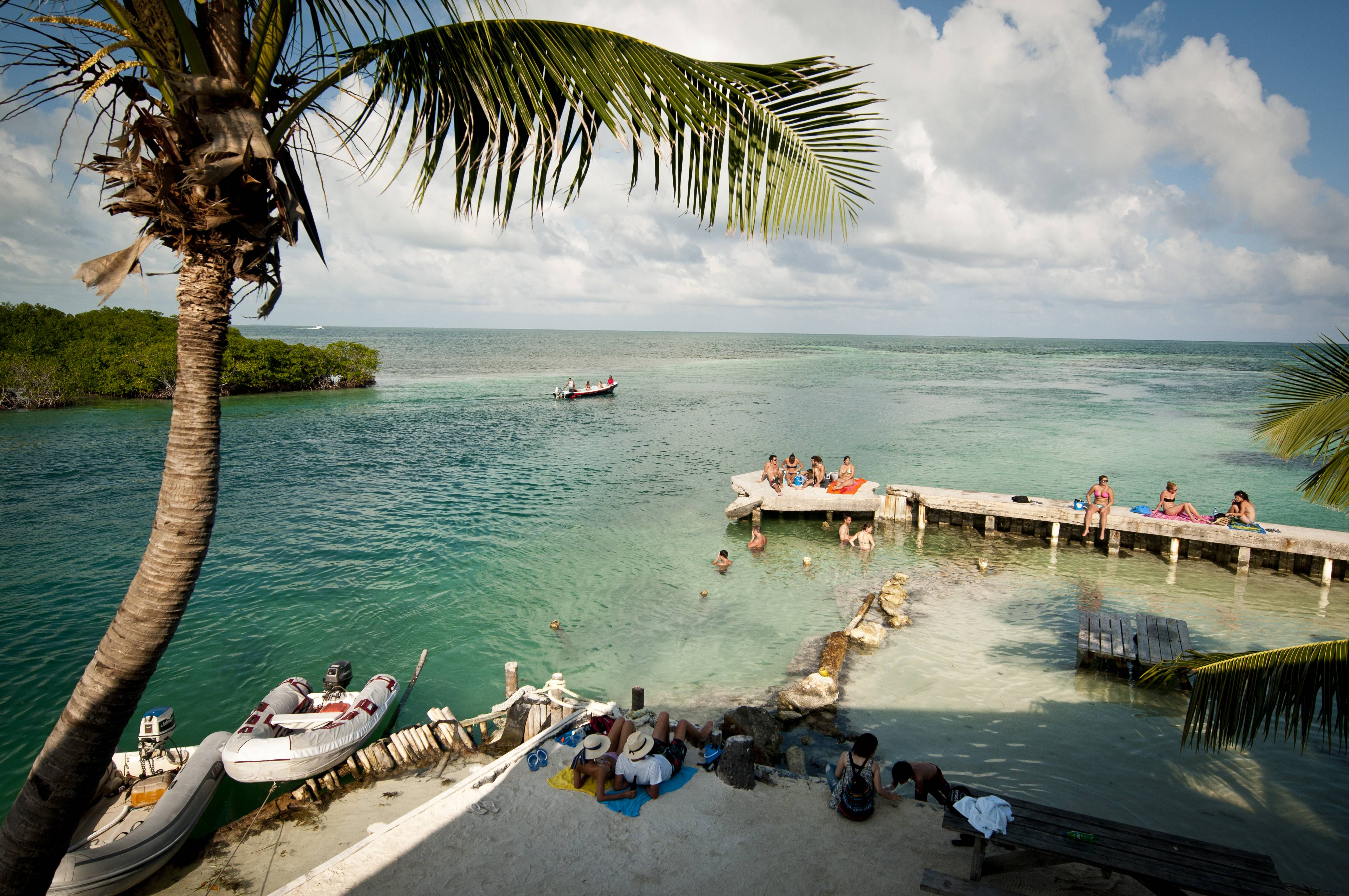 Vacationers relax at Caye Caulker, Belize. The beach town is a laid-back, low-cost base for tourists looking to explore a nearby barrier reef.