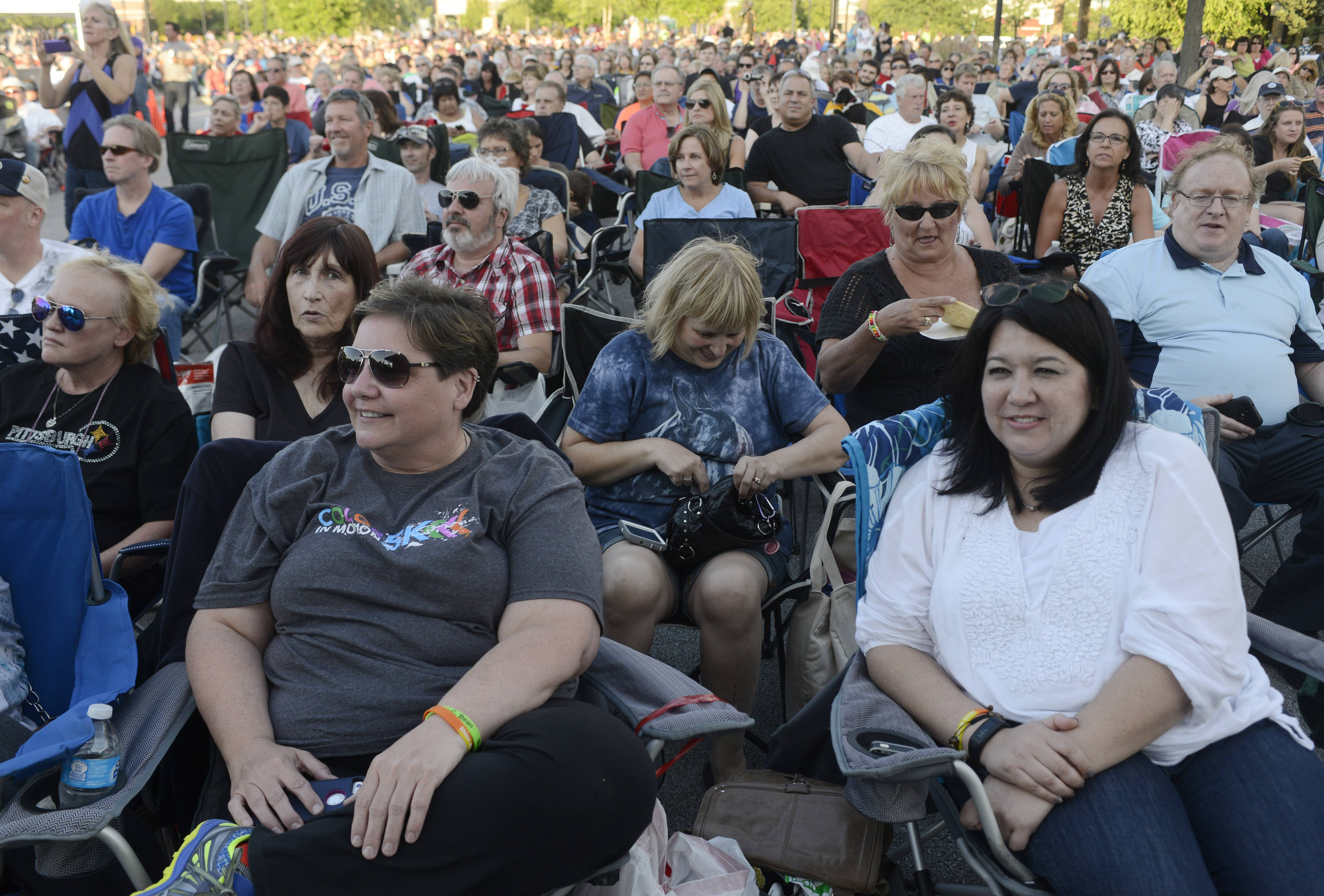 "Audience members watch as the band ""America"" performs during the Mid-Summer Classics Concert Series in Elk Grove Village Tuesday."