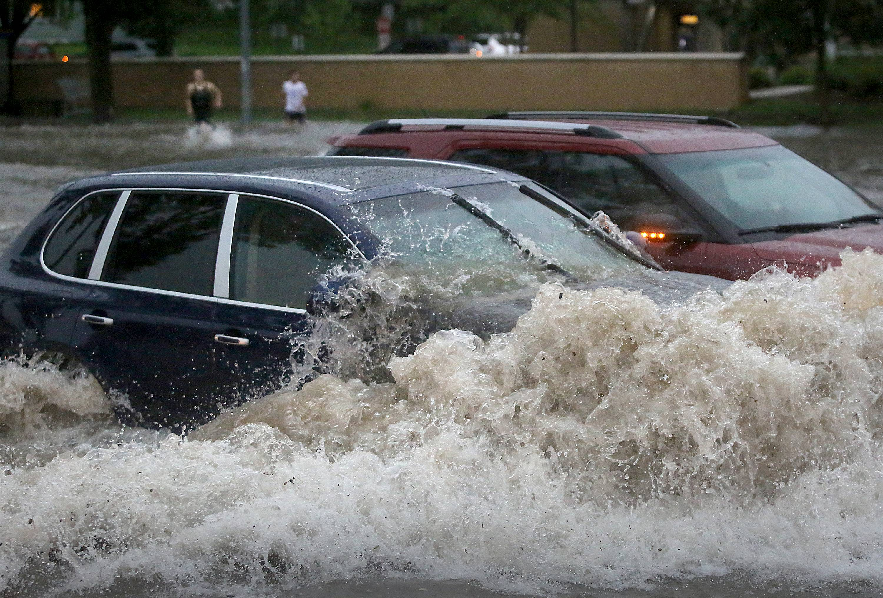 A car attempts to make its way through the flooded intersection of University Boulevard and North Midvale Road in Madison, Wis., after heavy rain moved through the area Monday. Severe thunderstorms packing high winds and heavy rain have downed trees and power lines all across southern Wisconsin.