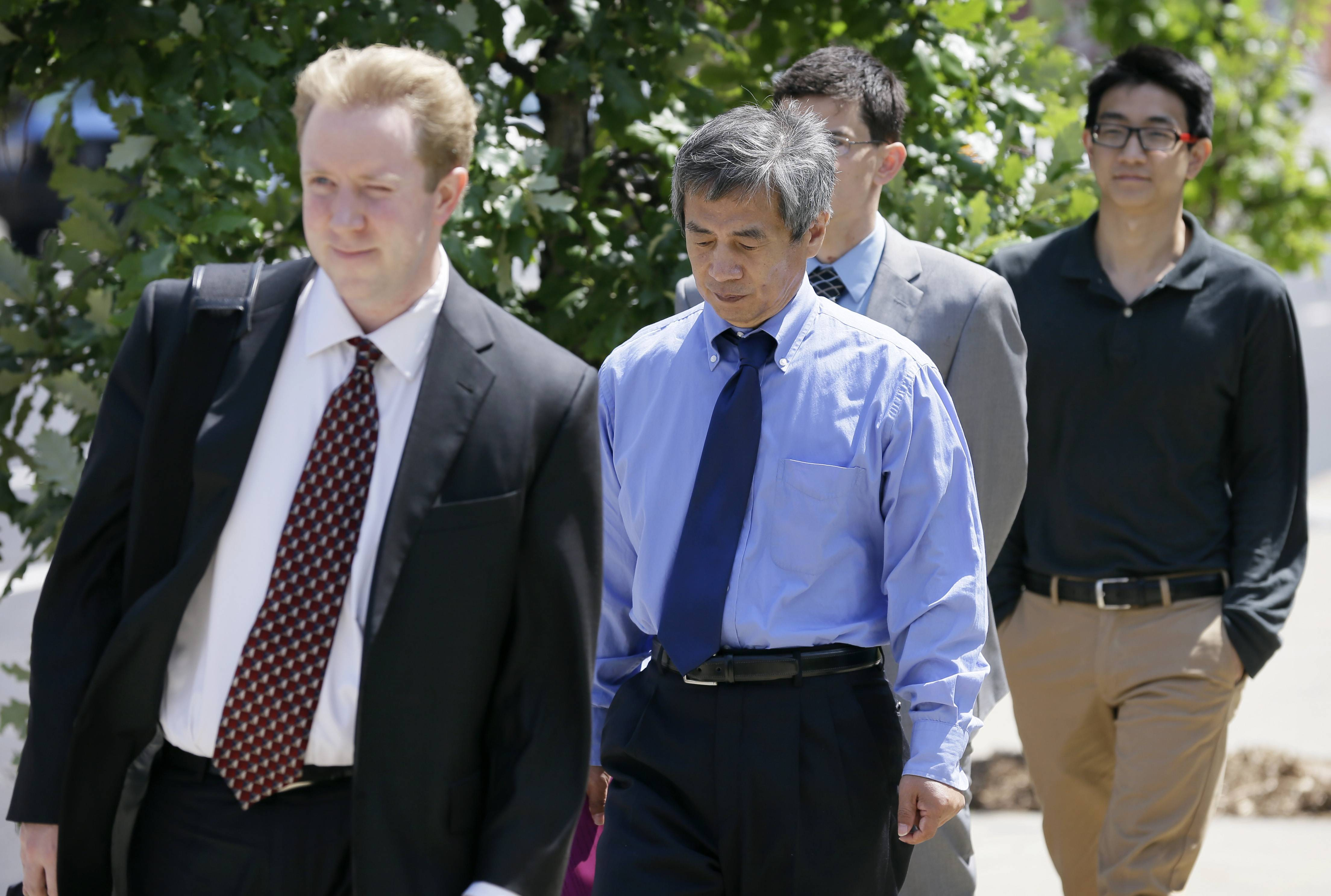 Former Iowa State University researcher Dong-Pyou Han, center, leaves the courthouse with his attorney Joe Herrold, left, Tuesday in Des Moines, Iowa. Han was making his initial court appearance on charges that he falsified data to make a proposed AIDS vaccine appear promising and win millions of dollars in federal grant money.