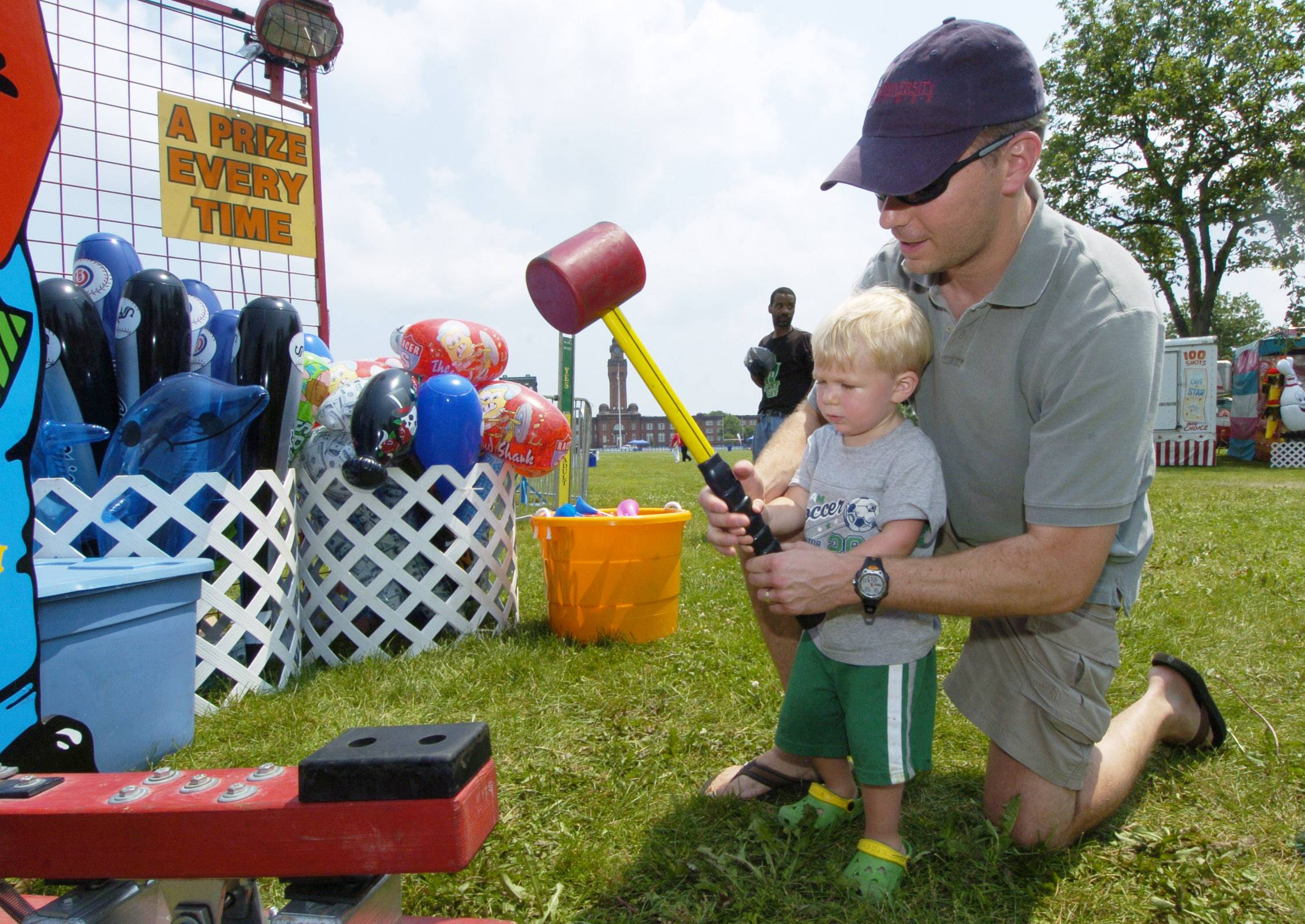Truman Anderson gets help from his dad, Navy LCDR Scott Anderson, as they play a game during Great Lakes Naval Station's 100th anniversary celebration in 2011.