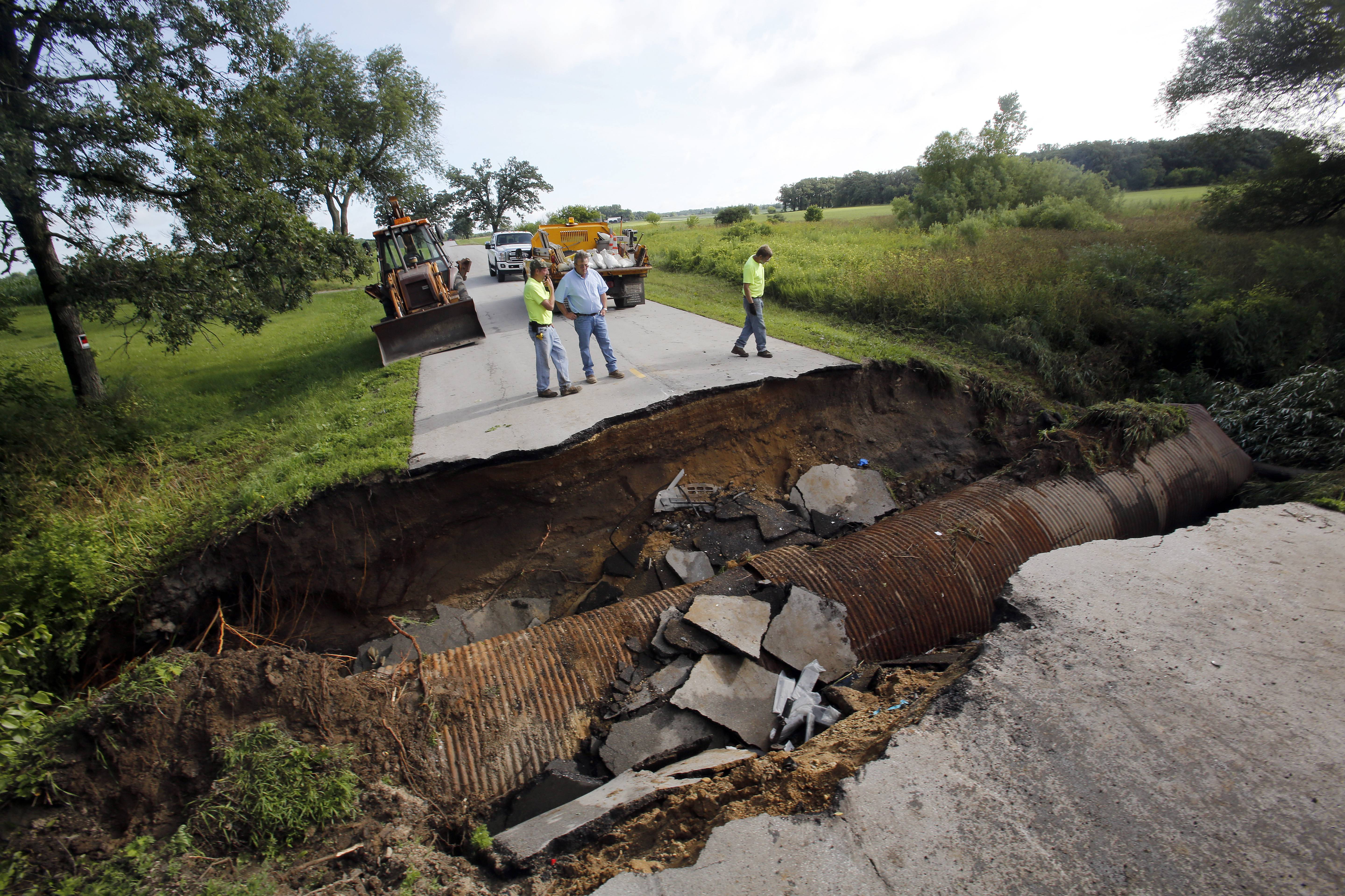 Kane County crews look over a sink hole on Thomas Road in Kane County Tuesday morning. Two cars were entrapped in the hole after driving into it earlier this morning.