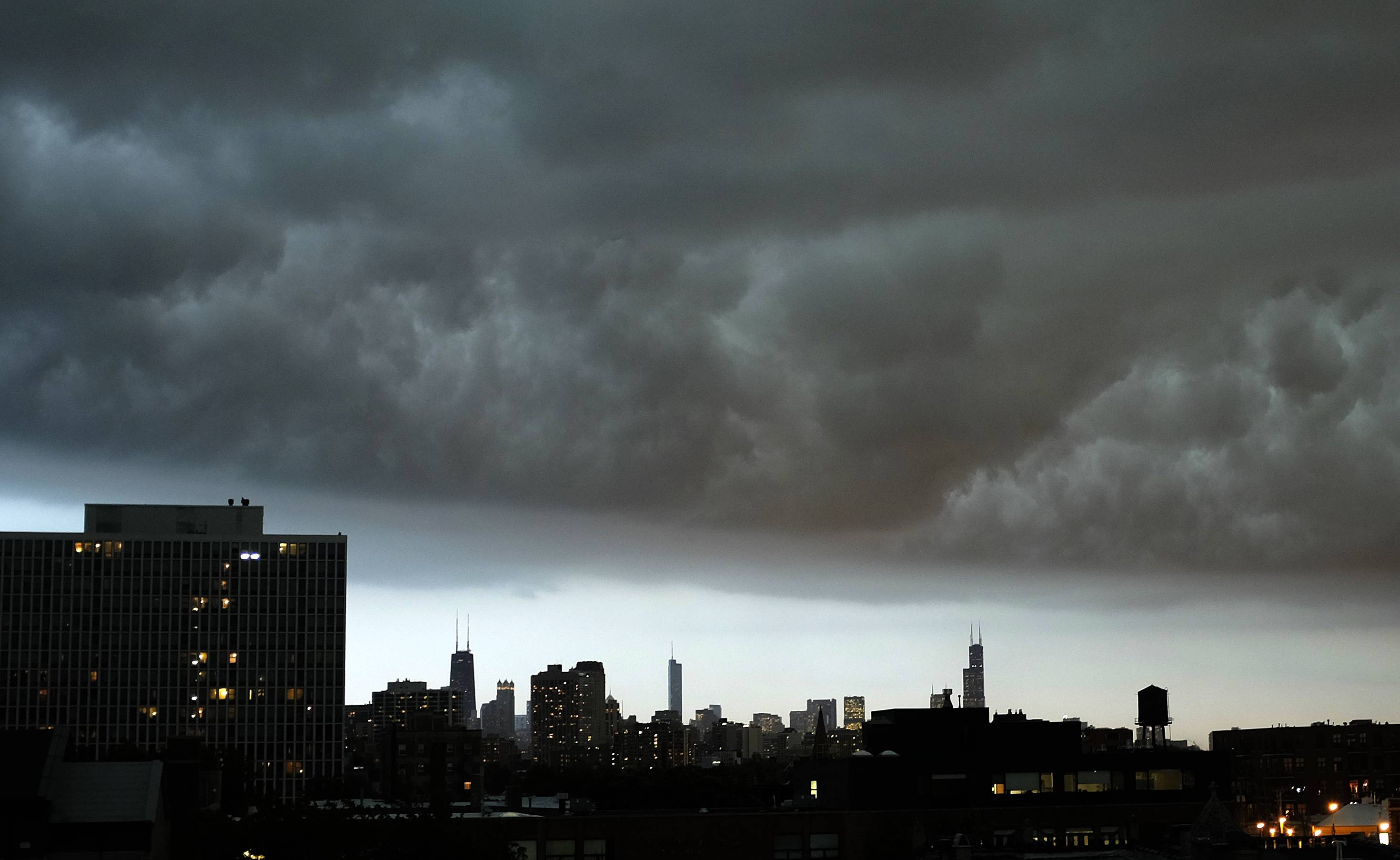 Storm cloud hangs over downtown Chicago skyline Monday evening as rain and high winds moved into Illinois from Iowa. Flights cancelled at Chicago's O'Hare International Airport as northern Illinois braces for severe weather.