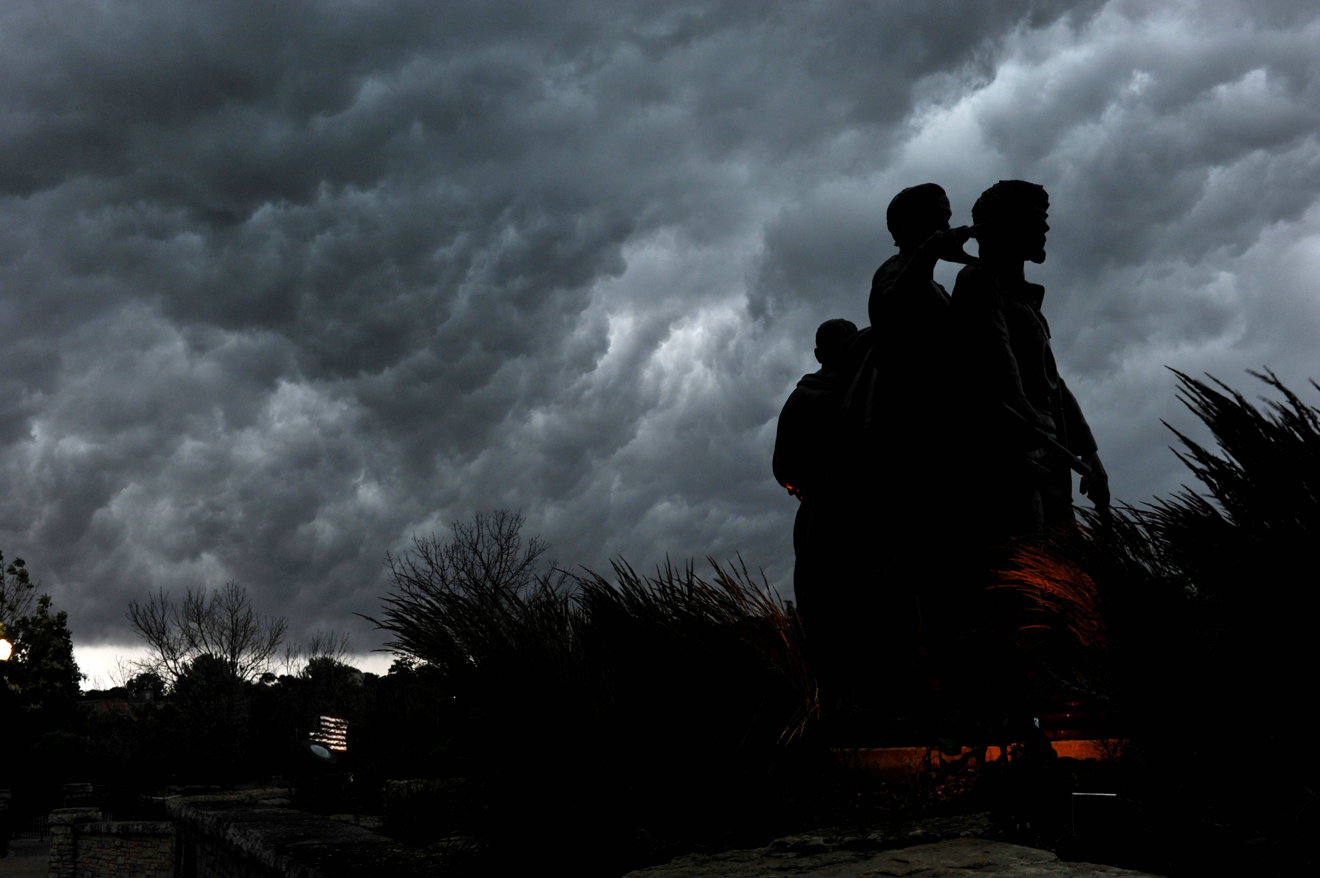 Dark storm clouds roll in near the Pioneer Family Memorial on the Fox River in Elgin on Monday evening.