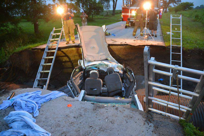 Rescue crews look over the car that sits in a sinkhole Tuesday morning in Kane County.