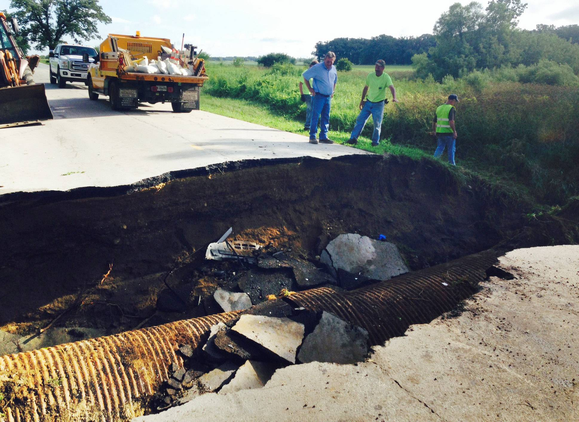 An Elgin mother and her teenage son narrowly avoided tragedy early Tuesday morning when their car plunged into a sinkhole along a washed-out rural Kane County road and then was run over by a pickup truck.