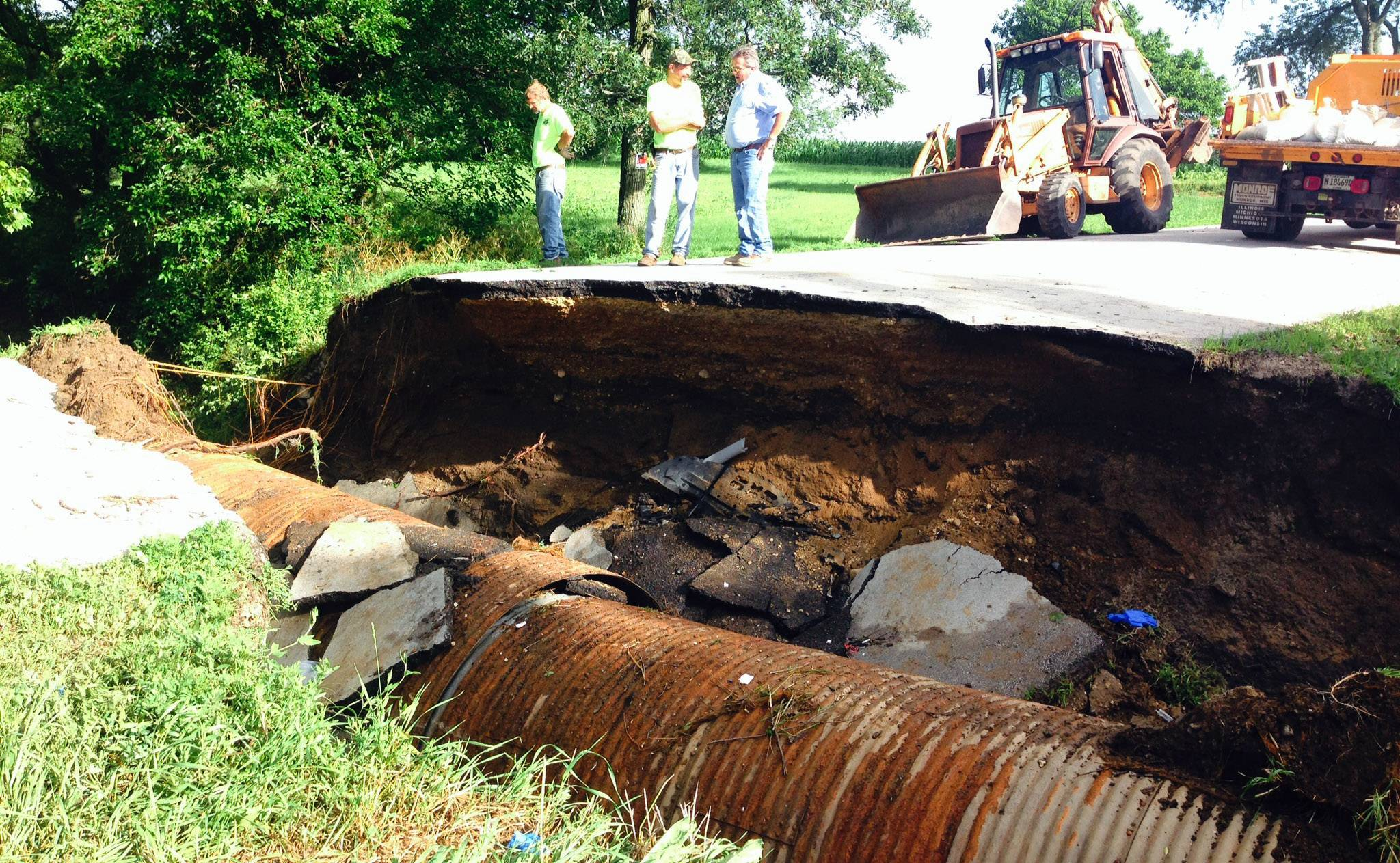 Road crews survey the damage at Thomas and McDonald roads in Kane County after storms washed out the road, creating a large sinkhole that a car later drove into.