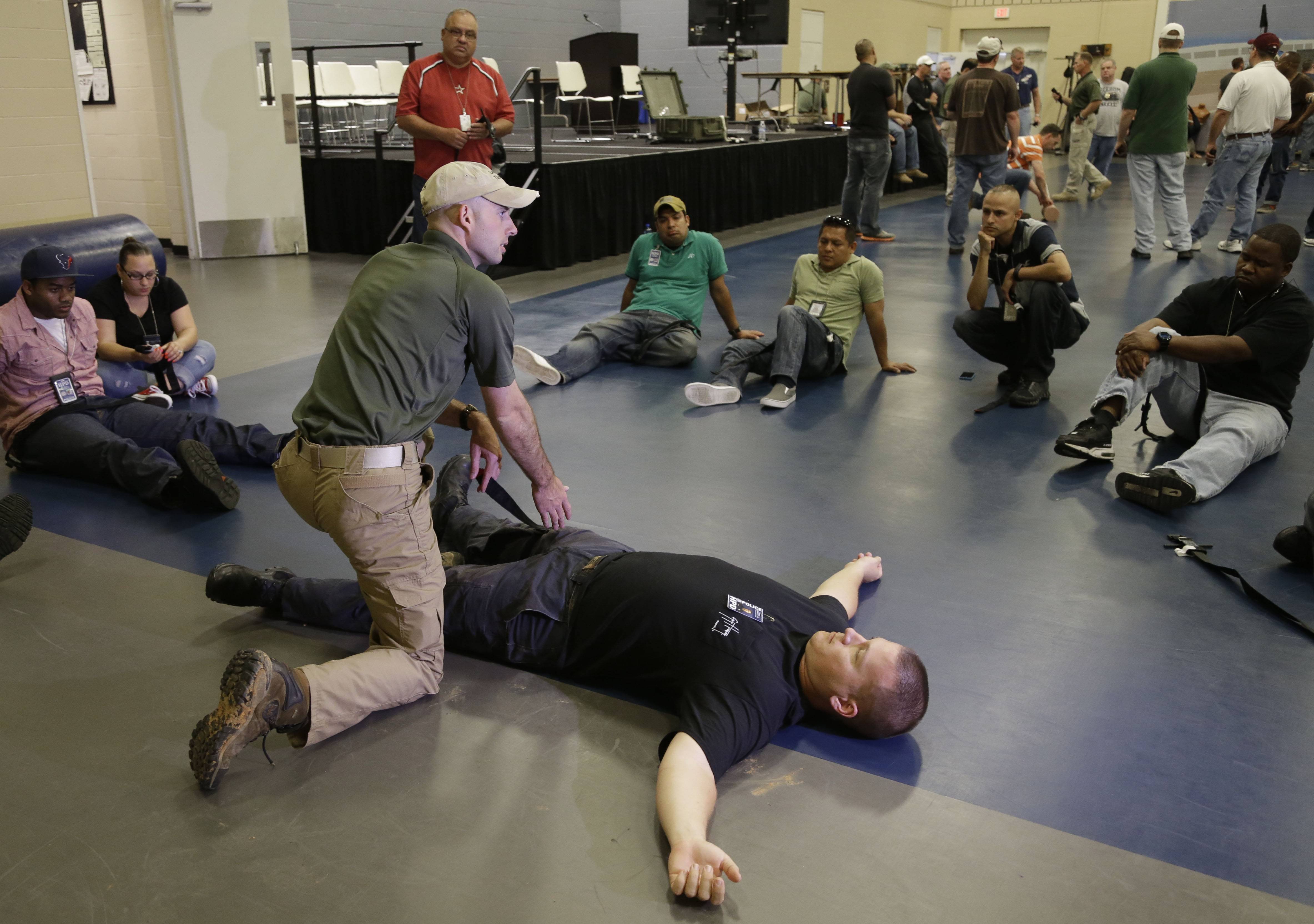 Houston police officer Austin Huckabee, left, uses officer Thomas Emmite, Jr, to show other officers how to apply a tourniquet at the police academy in Houston. Cities across the country are training and equipping police officers to use tourniquets and combat gauze.