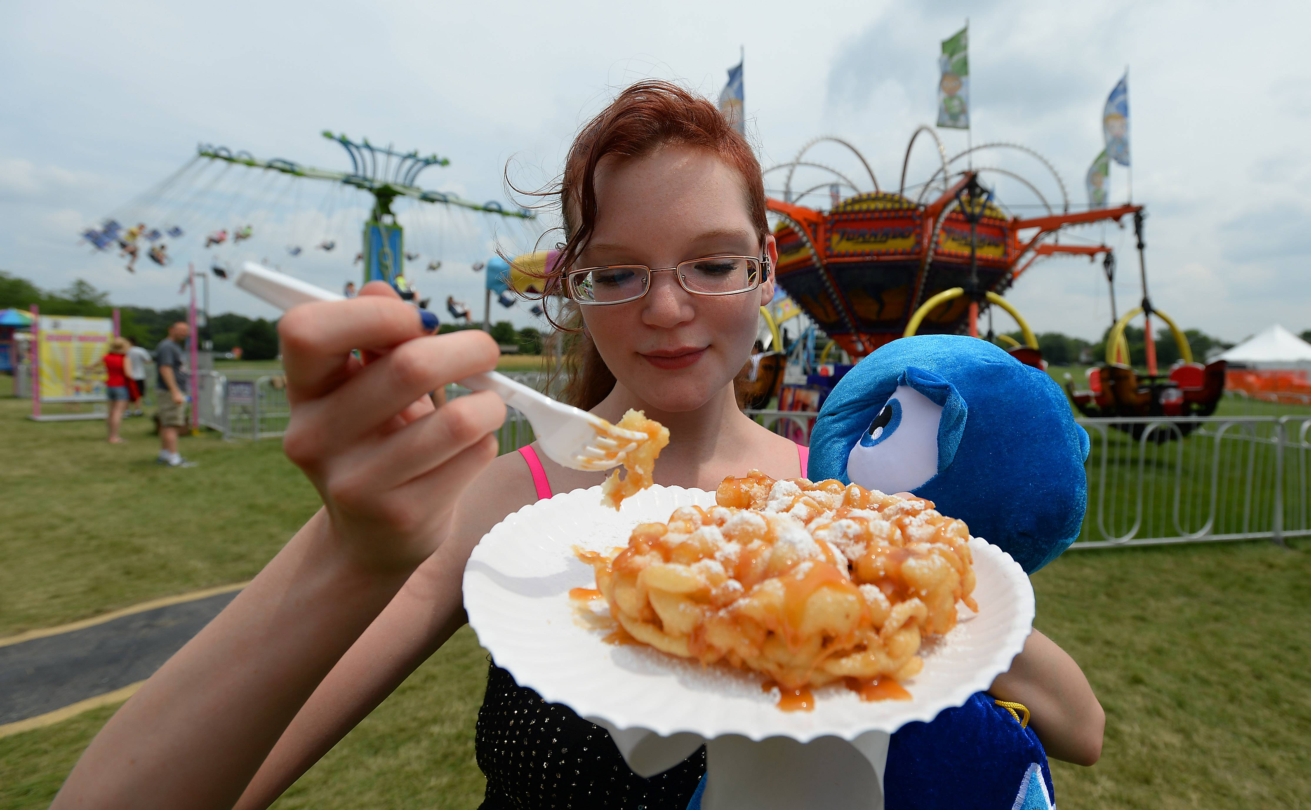 Funnel cake and caramel on a hot summer day is perfect for Katherine Kennedy, of Bartlett, as she enjoys the Bartlett Fourth of July Festival on Saturday.