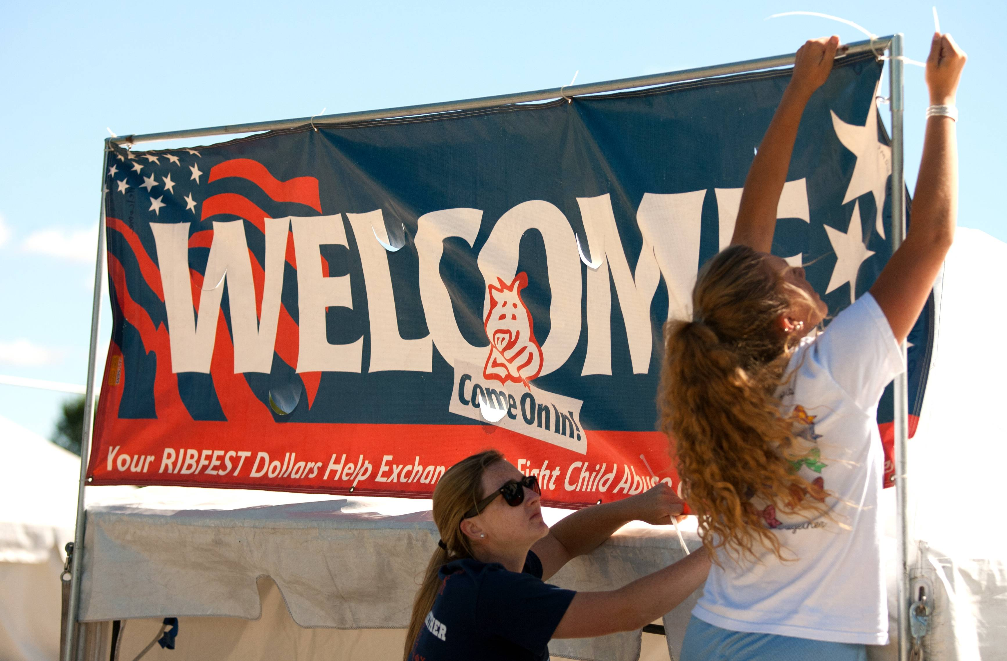 Juliet Tassi and Sarah Zimmerman help post a welcome sign Wednesday inviting visitors into Knoch Park for the 27th annual Ribfest in Naperville. The festival runs from noon to 10 p.m. Thursday through Sunday.