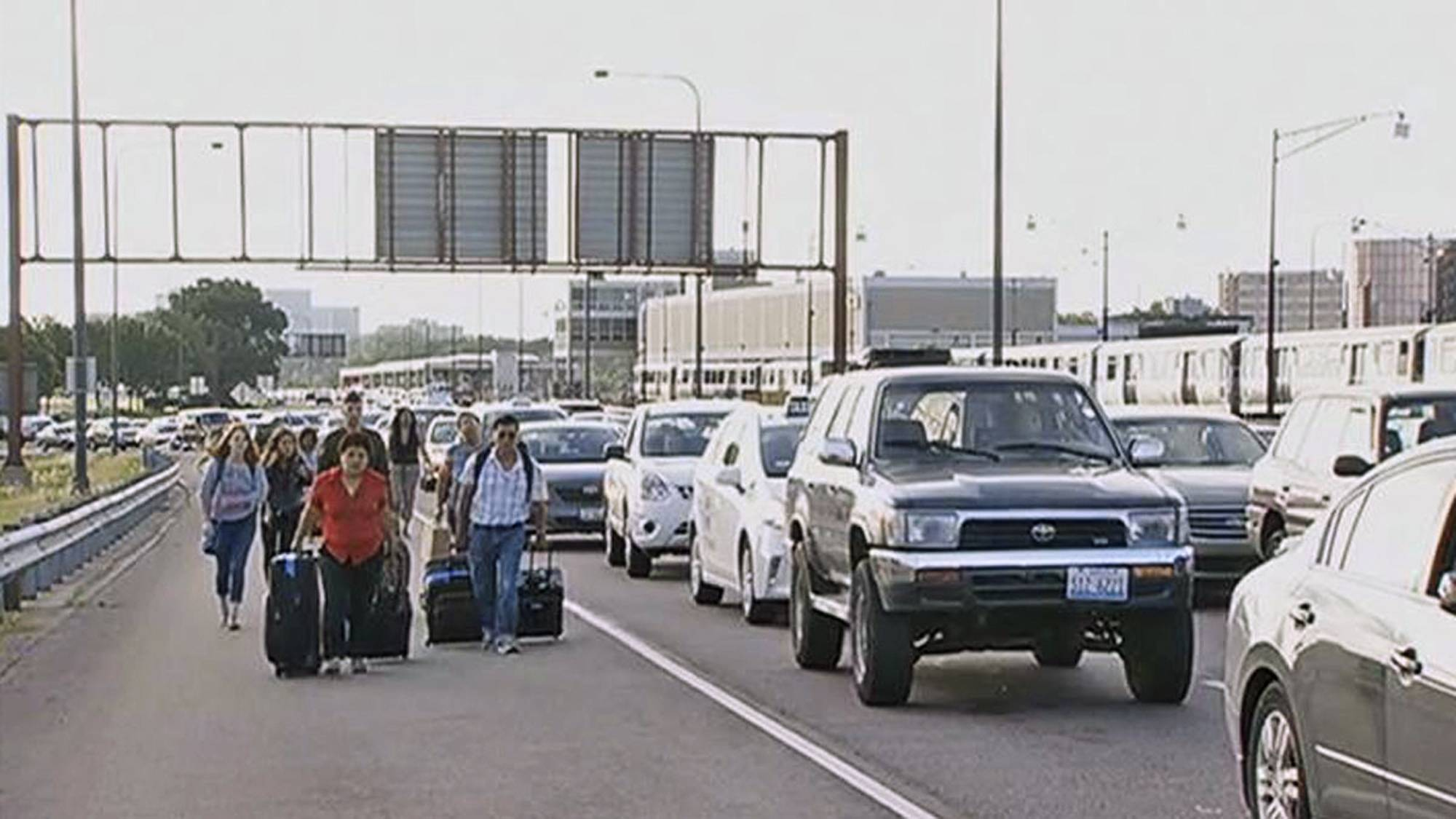 Air travelers wheeling their luggage toward Chicago's O'Hare International Airport Tuesday after sudden rains flooded the Kennedy Expressway Desperate travelers were forced to get out of taxis and haul their luggage the rest of the way to the airport.