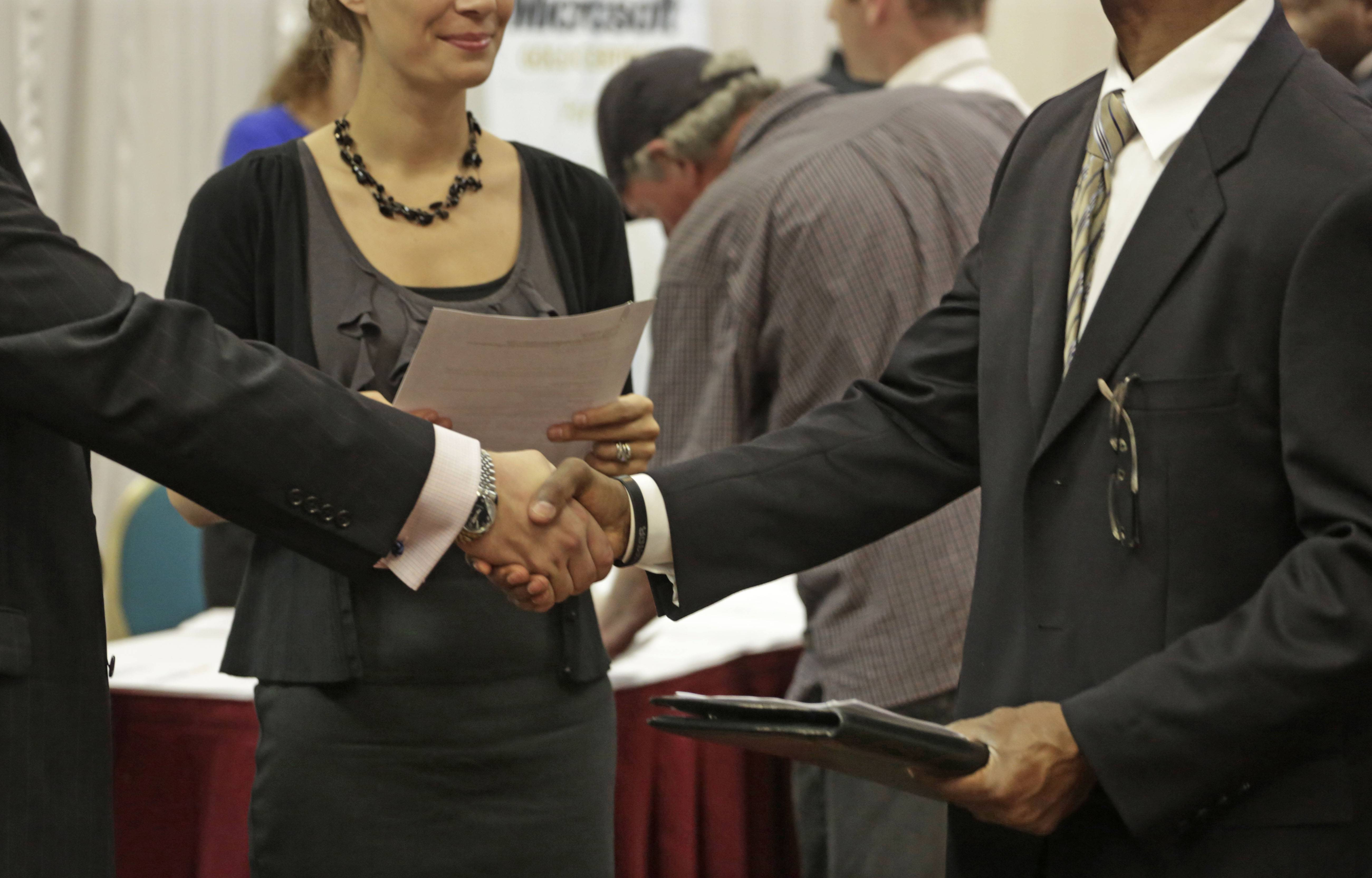 A job-seeker meets a possible employer at a job fair in Rolling Meadows in May 2013. Even though economists declared the recession over in June 2009, Illinois is still down 184,000 jobs from pre-recession levels.