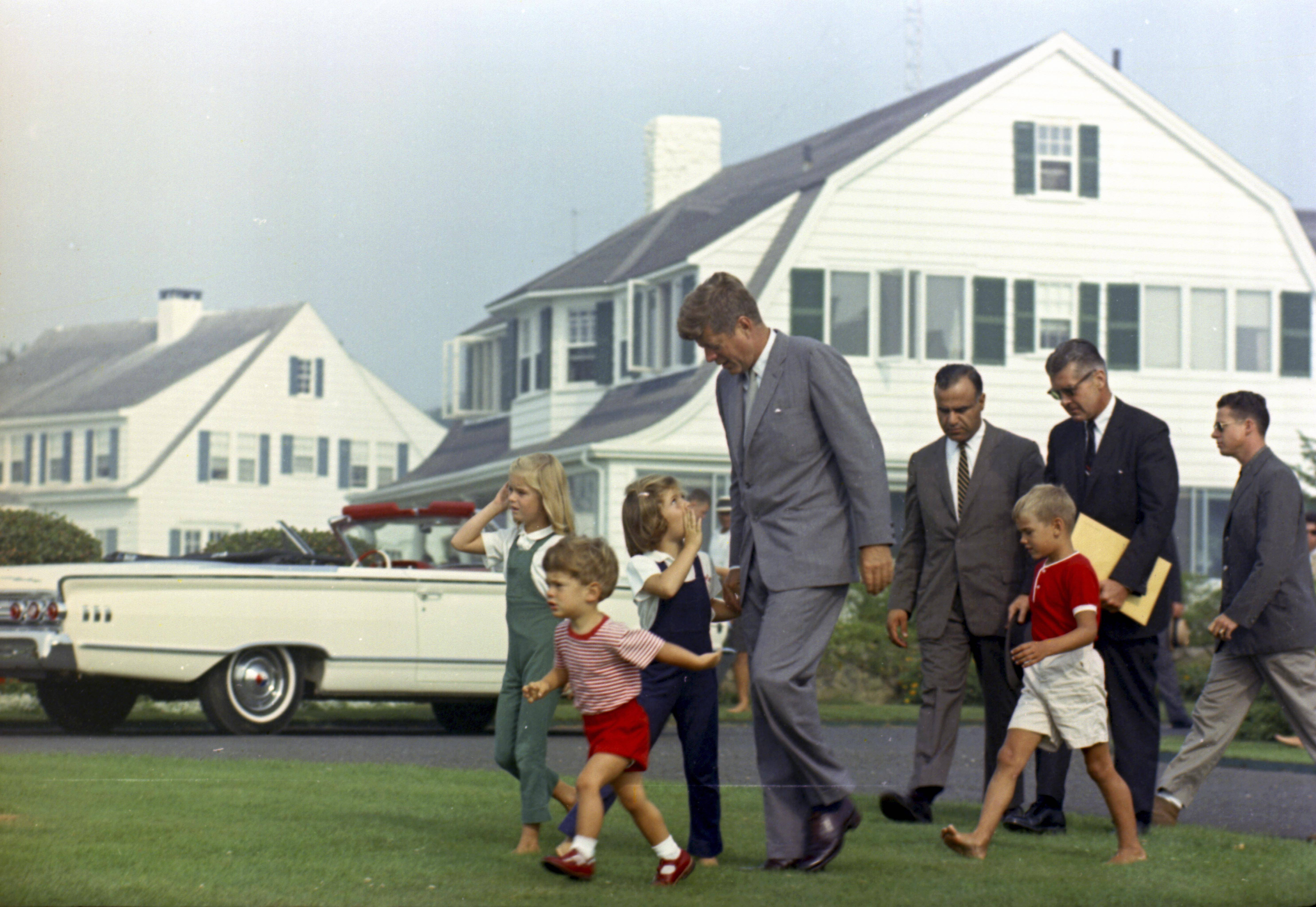 President Kennedy approaches a helicopter at the family home in Hyannis Port, Mass., for the first leg of his journey back to Washington in August 1963. Accompanying him are Sydney Lawford, left, John F. Kennedy Jr., Caroline Kennedy, the President, Secret Service Agent Sam Sulliman, David Kennedy, and Agents Jerry Behn and Tom Wells. The JFK library opened a special exhibit Friday featuring some never-before displayed artifacts from the Kennedy family's summers on Cape Cod.