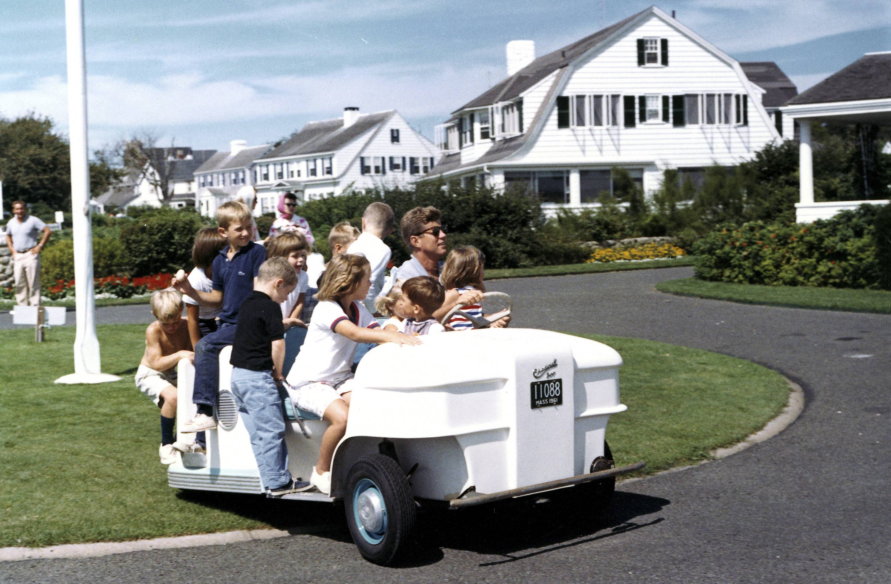 In this Sept. 3, 1962 photo, President Kennedy drives his nieces and nephews in a golf cart at the family home in Hyannis Port, Mass. The JFK Library opened a special exhibit Friday featuring some never-before displayed artifacts from the Kennedy family's summers on Cape Cod, including the golf cart.