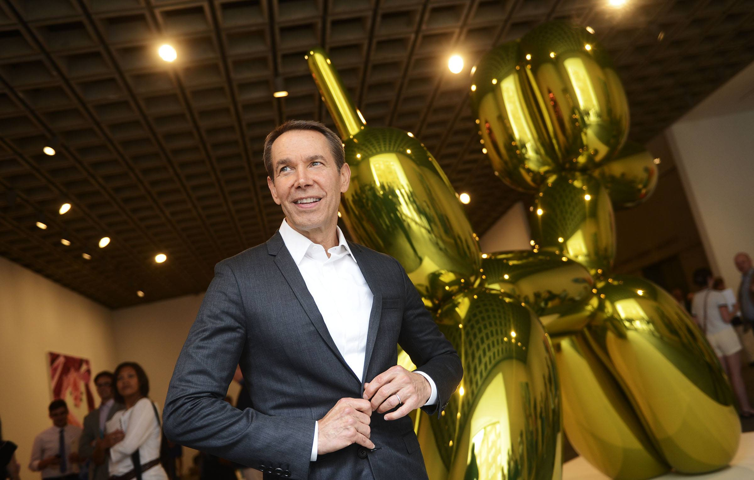 "Jeff Koons poses for photos in front of one of his pieces during the media preview of ""Jeff Koons: A Retrospective"" at the Whitney Museum of American Art in New York."