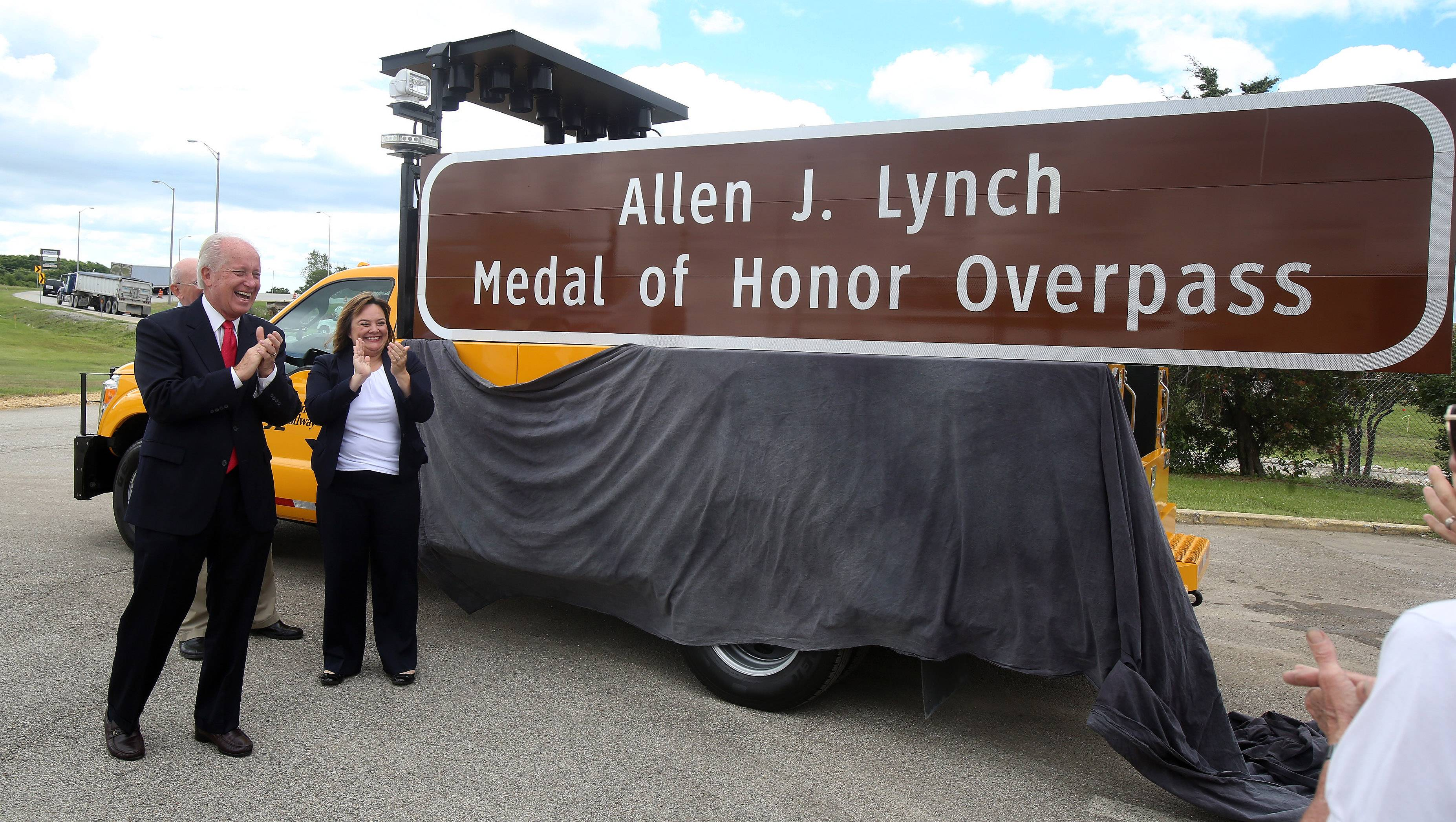 State Sen. Terry Link and Kristi Lafleur, executive director of the Illinois State Toll Highway Authority, applaud the sign marking the Allen J. Lynch Medal of Honor Overpass at Grand Avenue and the Tri-State Tollway in Gurnee. Lynch received the Medal of Honor for acts of valor during the Vietnam War.