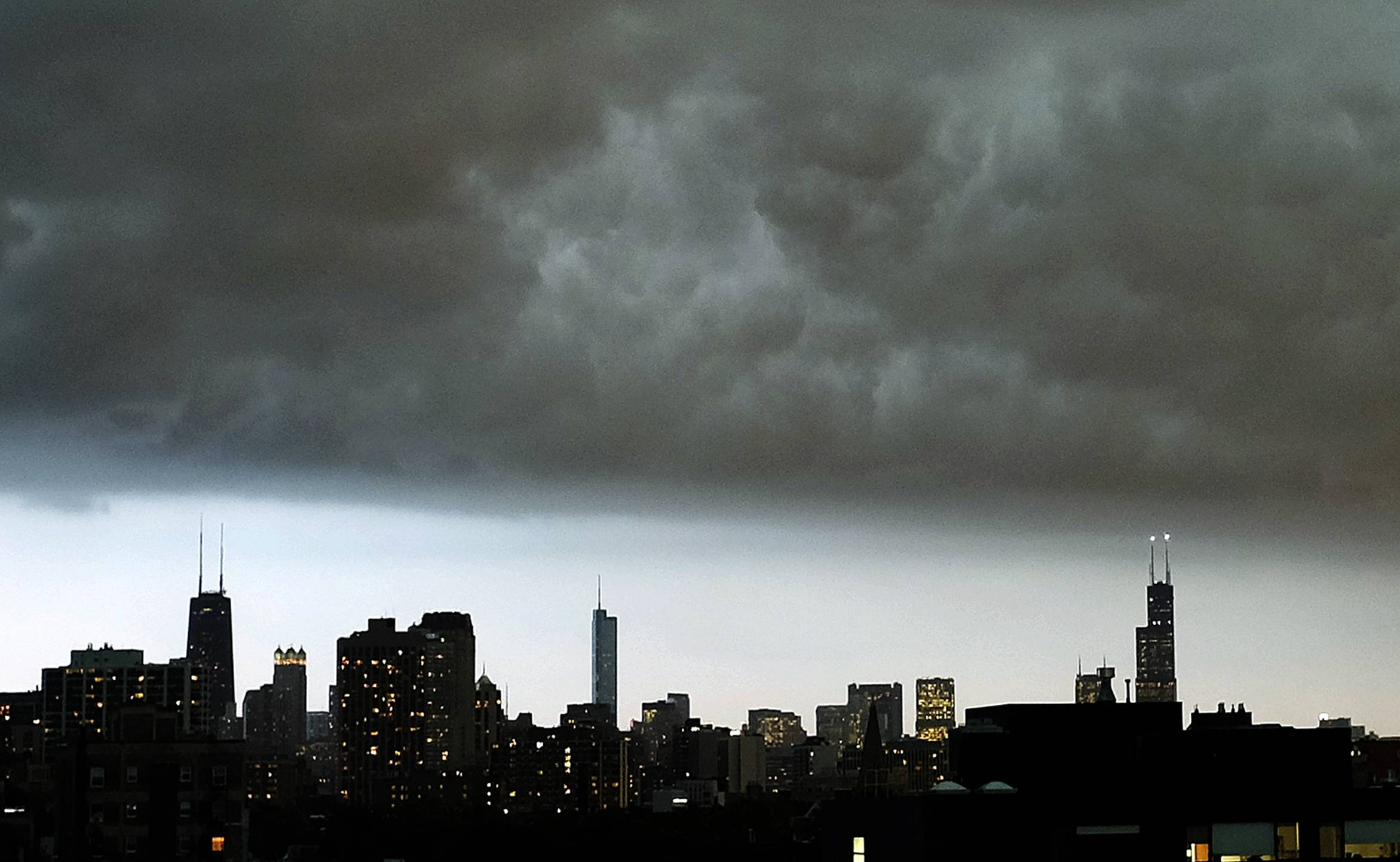 Storm clouds hang over the downtown Chicago skyline Monday. The National Weather Service is now reporting five tornadoes touched down in Illinois during a storm that dumped heavy rain as it swept across the state.
