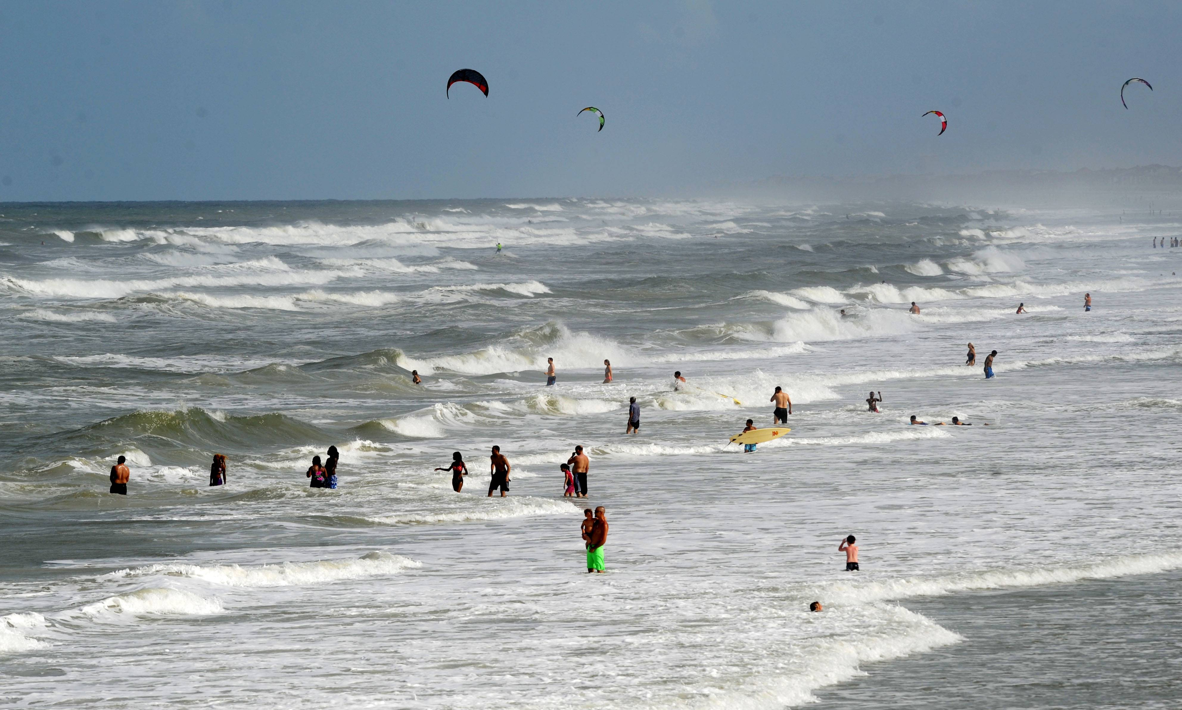 People enjoy the beach and heavy surf Wednesday at Jacksonville Beach, Fla. Tropical storm Arthur moved off the coast of Florida and headed to the Carolinas.