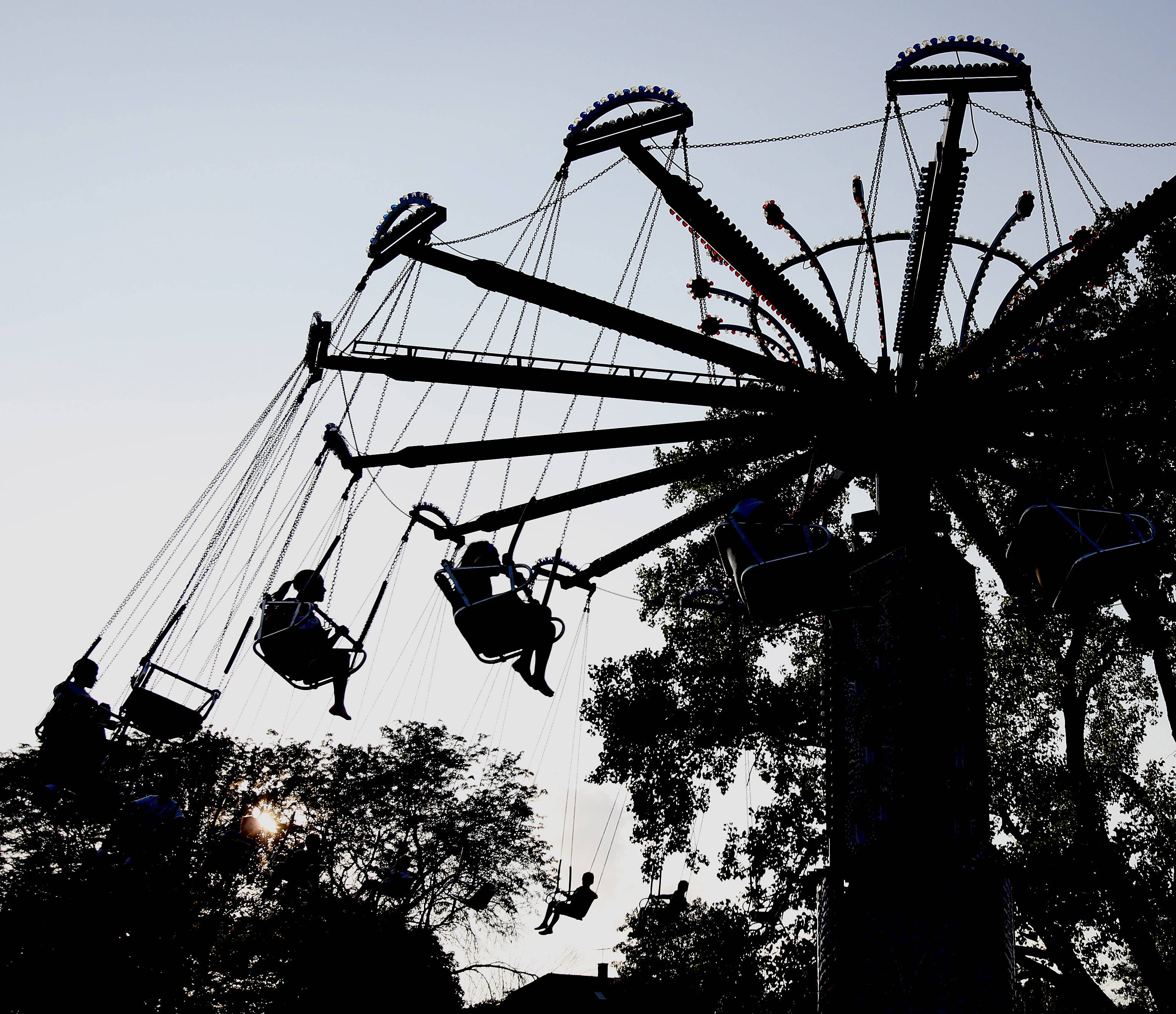 Visitors take a spin on the swing ride during opening day of Taste of Lombard on Tuesday.