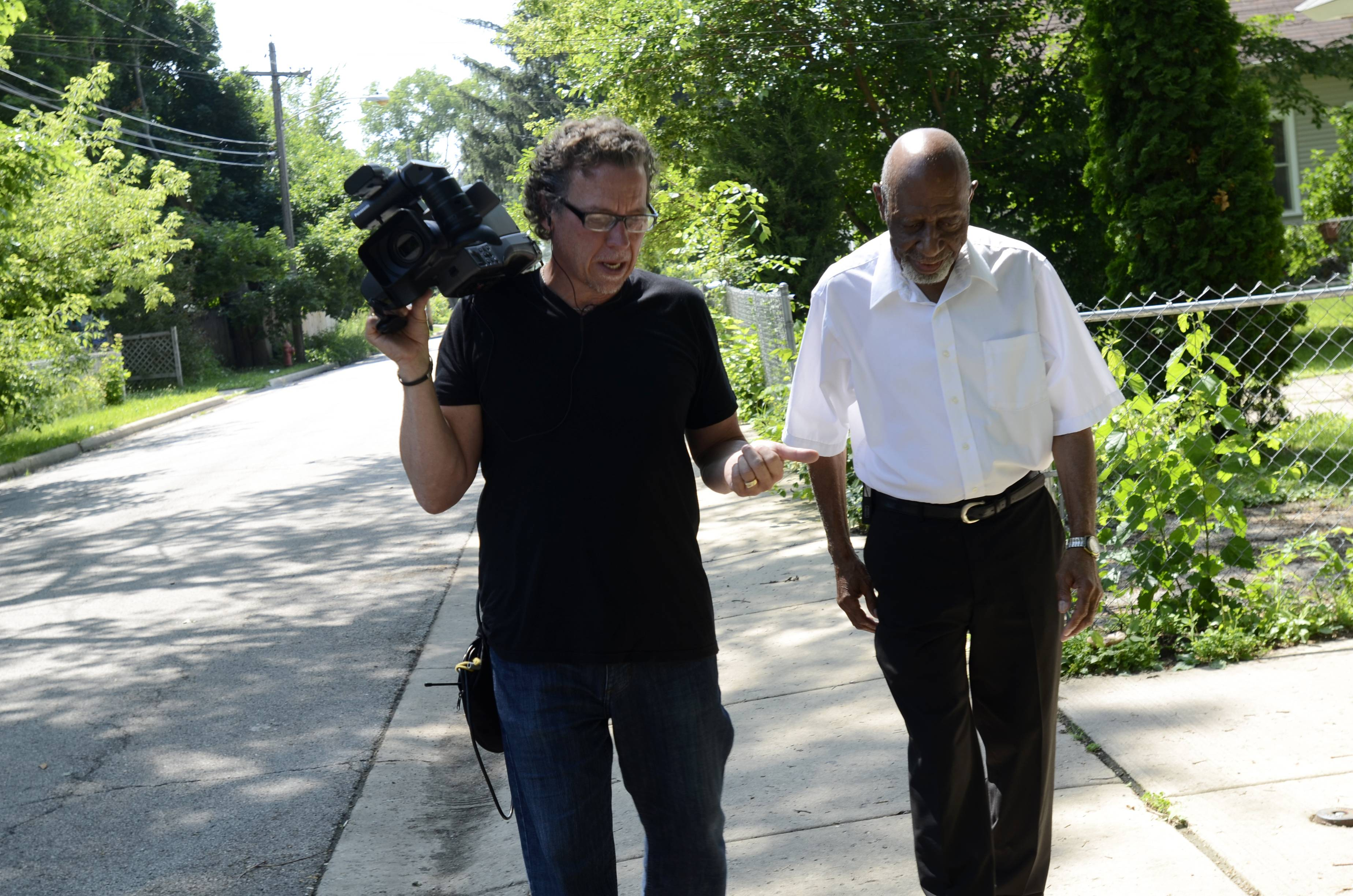 "Phil Broxham, left, and Ernie Broadnax, both of Elgin, walk down Hickory Place in Elgin. The two are filming a documentary called ""Project 2-3-1"" about what life was like for blacks before the Civil Rights Act was passed. Broadnax is a lifelong resident of the three-block Elgin neighborhood called ""the settlement,"" where most of the city's blacks lived throughout the 20th century."