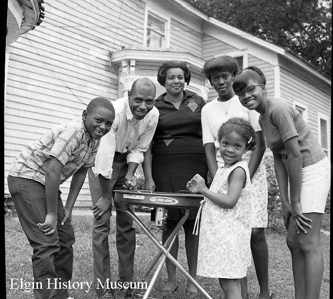 "Before the Civil Rights Act was passed, most of Elgin's black families lived in a three-block neighborhood known as ""the settlement."" This undated photo shows a barbecue with Fremont Activities Association members Ernie Broadnax, Terry Green, Evelyn Hopkins, Debbie Lathen, Denise Kennedy and Lisa Broadnax."