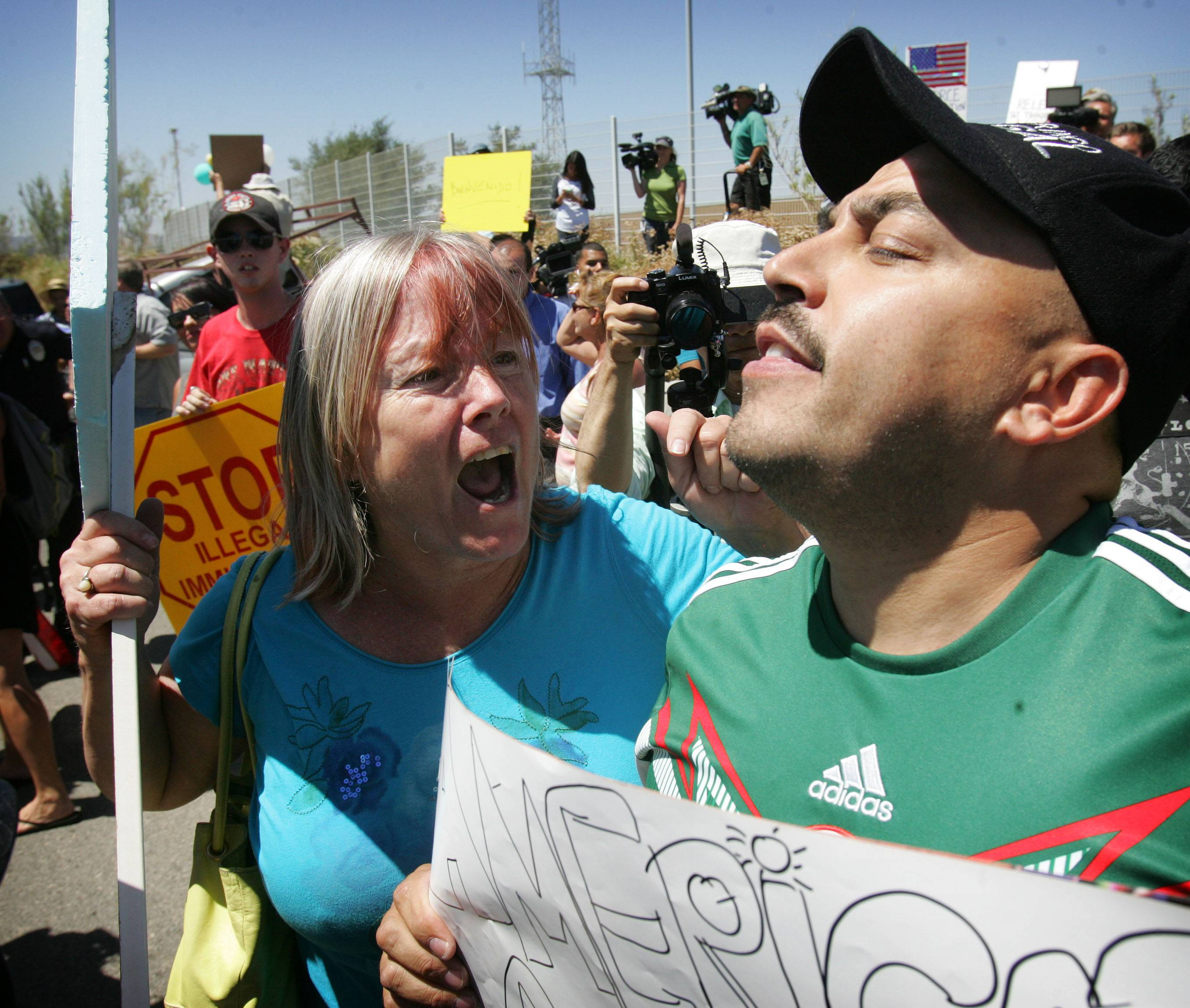 A protester, left, argues with American citizen Lupillo Rivera, brother of Mexican-American singer Jenni Rivera, right, as three buses carrying 140 immigrants attempt to enter the Murrieta U.S. Border Patrol station for processing Tuesday.