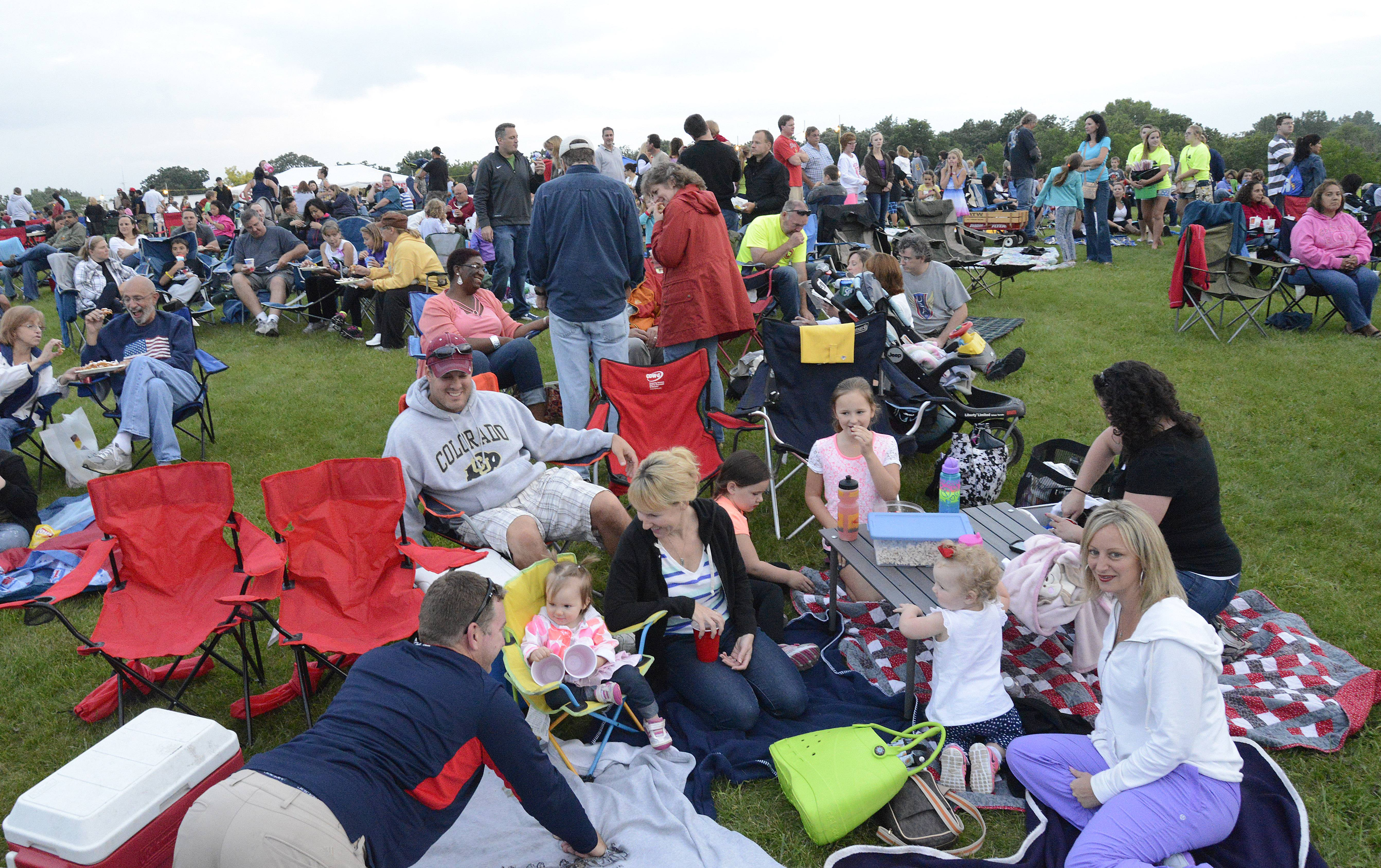 The Johnson and Dumele families of Cary and the Barnum family of Barrington camp out listening to music while they wait for the fireworks at Cary's Summer Celebration in Lions Park -- which is always held on July 3.