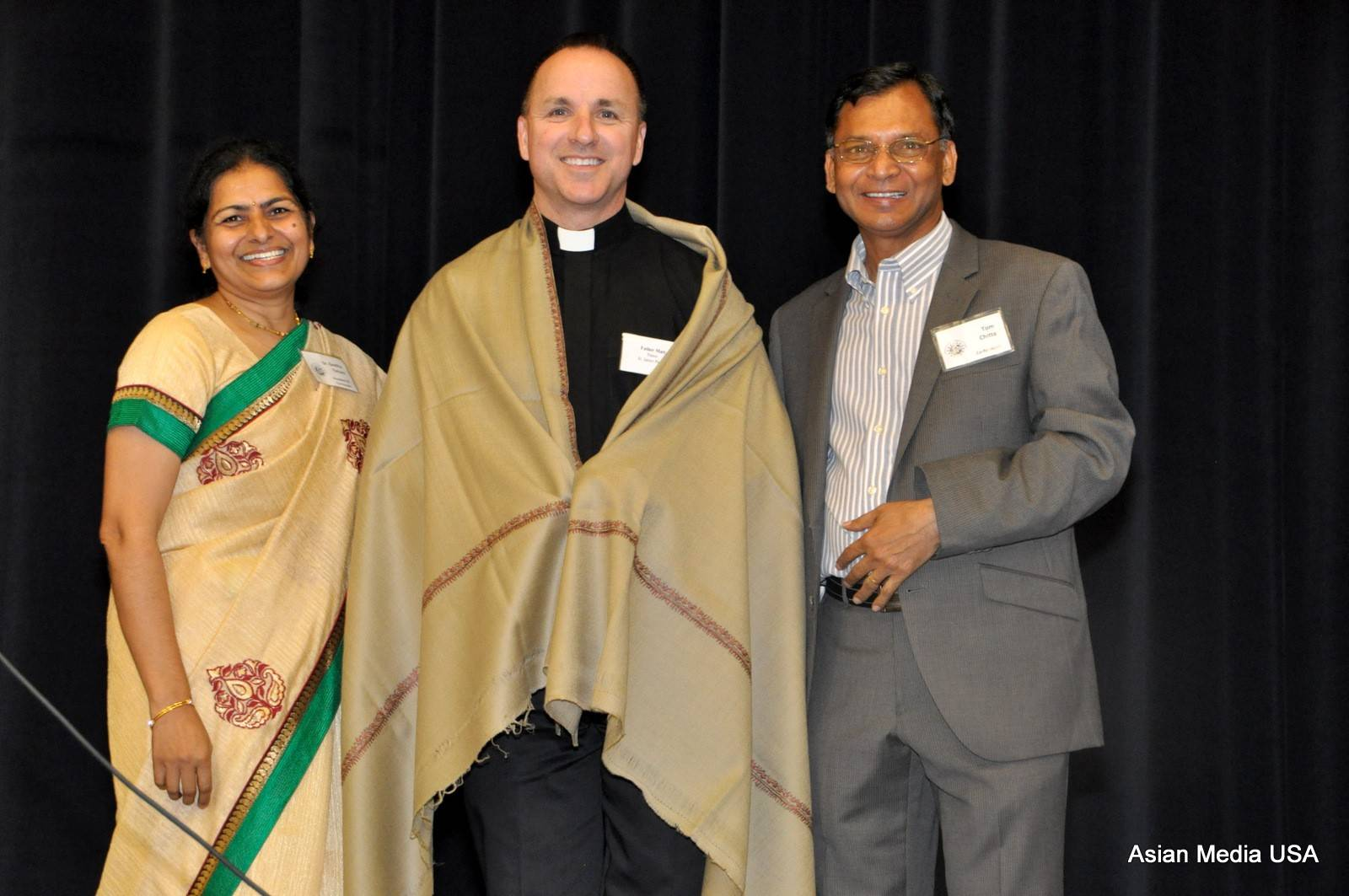 Dr. Geetha Yeruva, left, and Tom Chitta, right, founders of the Foundation for Children in Need with Father Matt Foley, pastor of St. James Parish in Arlington Heights at the foundation's 12th anniversary celebration.
