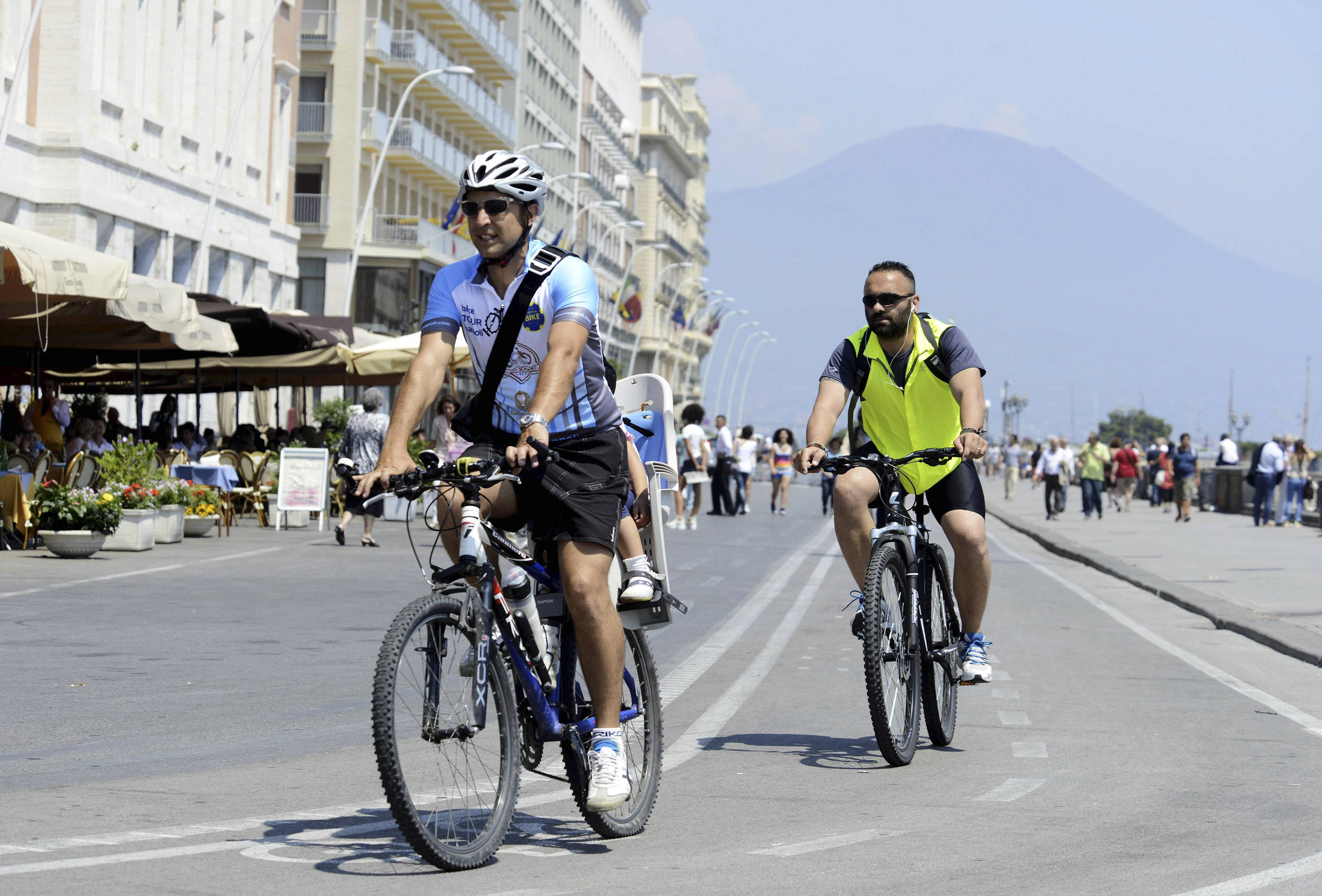 "Luca Simeone, left, founder of bike-sharing start up called ""bike tour Napoli,"" pedals along a cyclists' path in Naples, Italy. In the background is Mt. Vesuvius."
