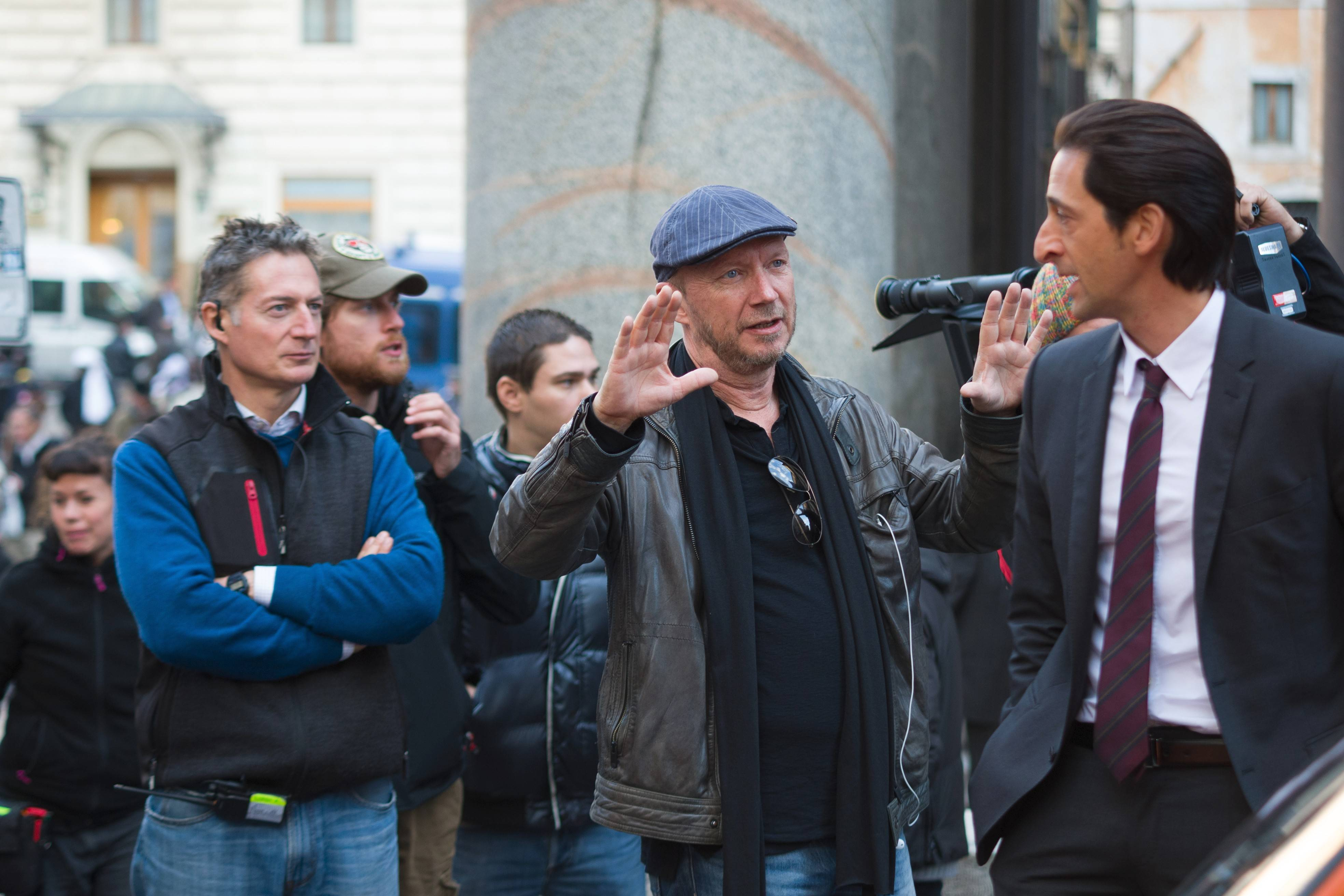 "Director/writer Paul Haggis, center, interacts with Adrien Brody on the set of ""Third Person."""