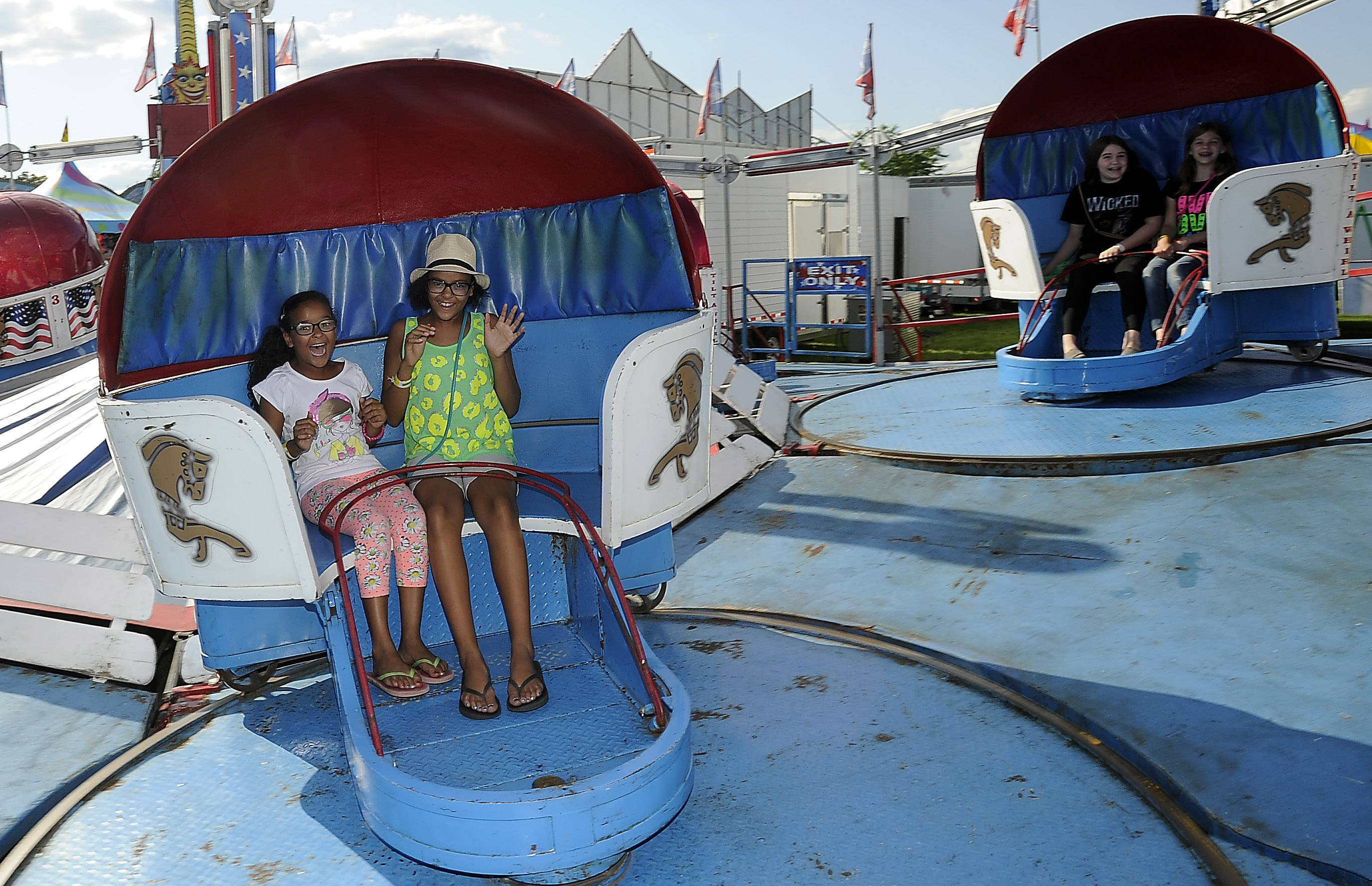 Monica Pedila, 8, of Bartlett and her sister Hania, 11, ride the Tilt A Whirl on Thursday at Bartlett's Fourth of July Festival.
