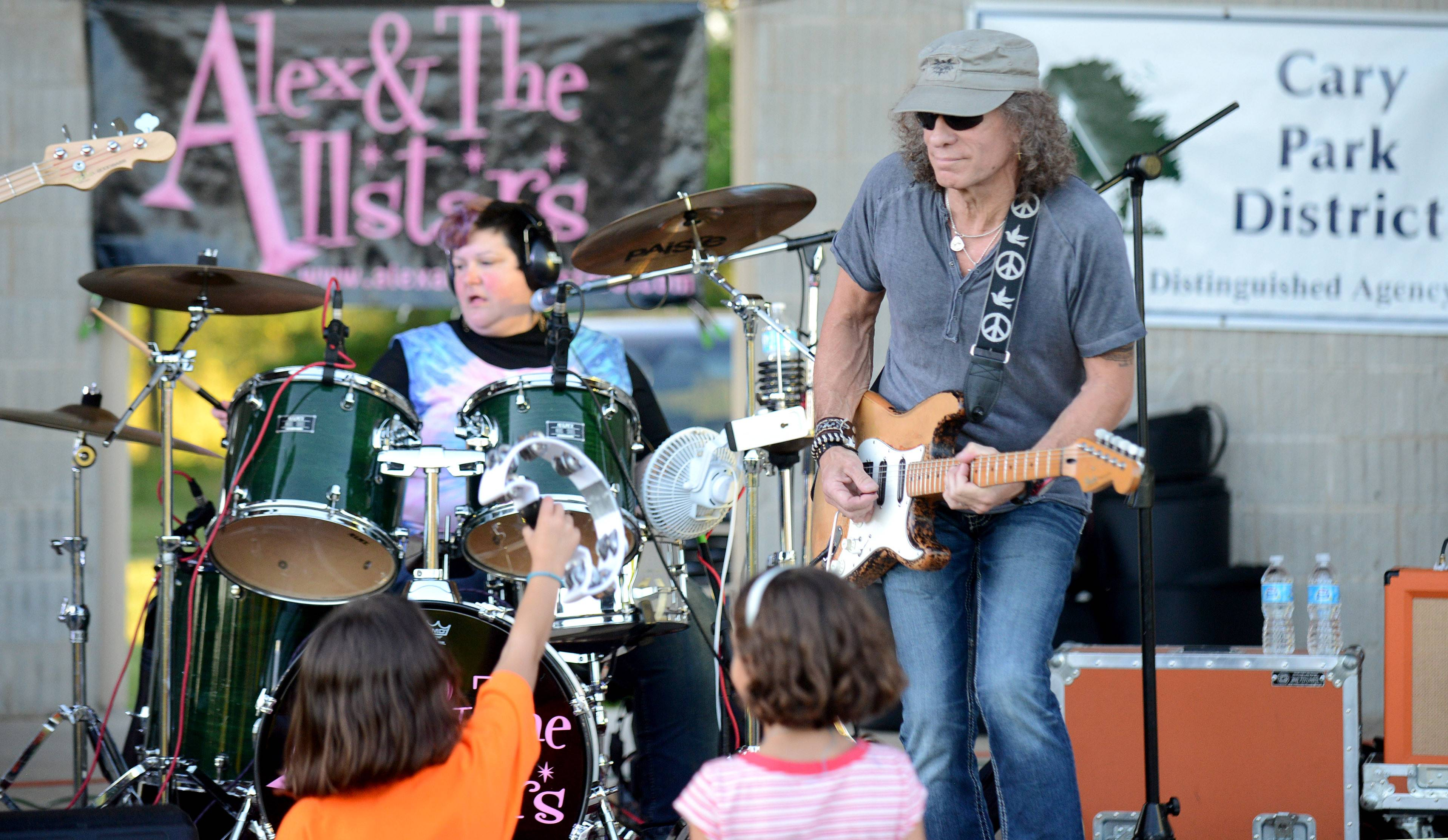 Alex Stanco on lead vocals and drums and Buddy Wiegelman on lead guitar, both of Fox River Grove, play to fans big and little Thursday during the Cary Summer Celebration at Lions Park. The band, which includes Lisa Lamanna of Kildeer and Bob Osters of Hoffman Estates, not shown, plays often summer concert series.