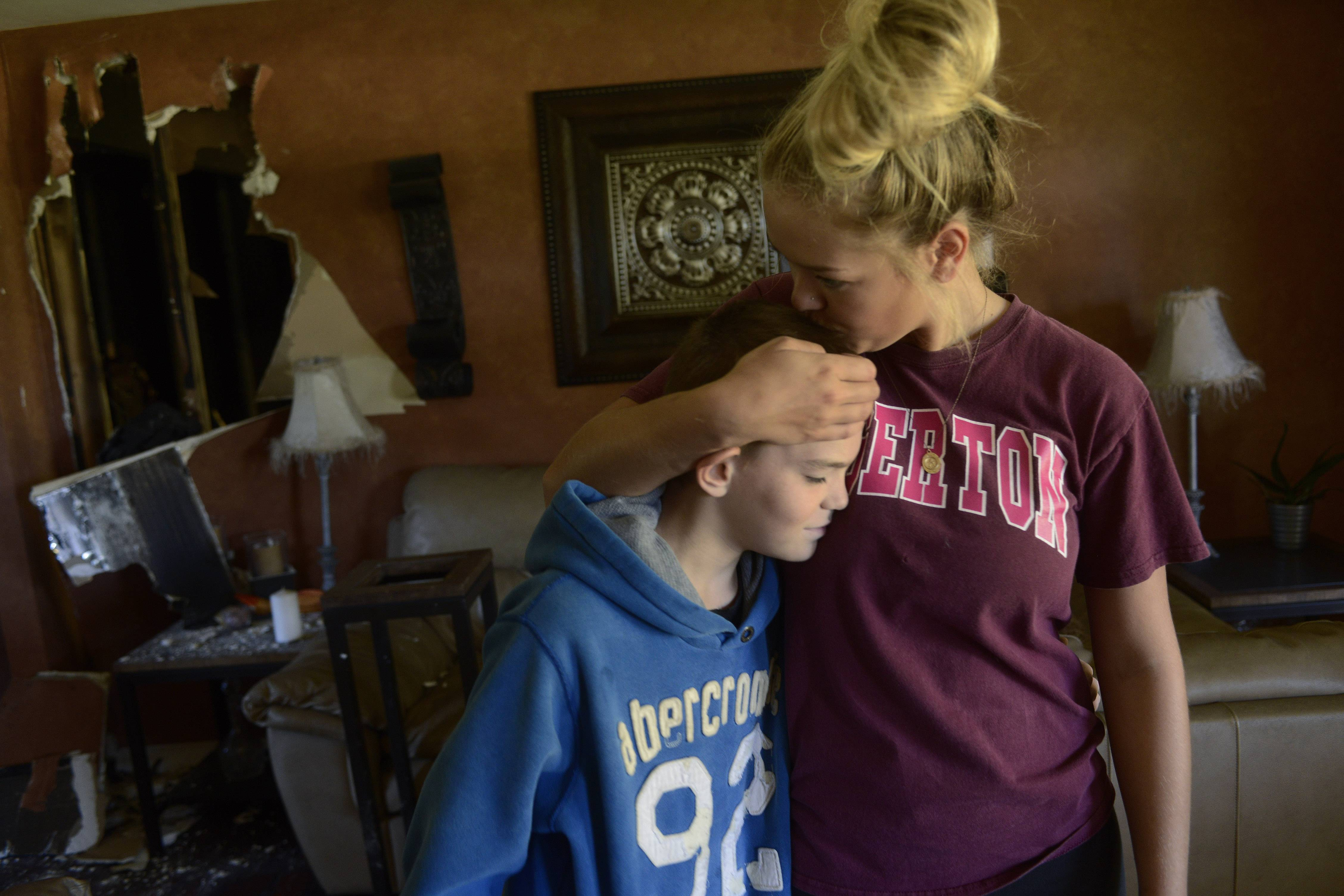 Jessica Lotesto gives her 13-year-old brother Dominic Laskero a kiss on top of his head as they reflect on their escape from a fire in their Hoffman Estates home Sunday morning. Nicky was instrumental in getting his sister and 77-year-old grandmother out of the burning house.