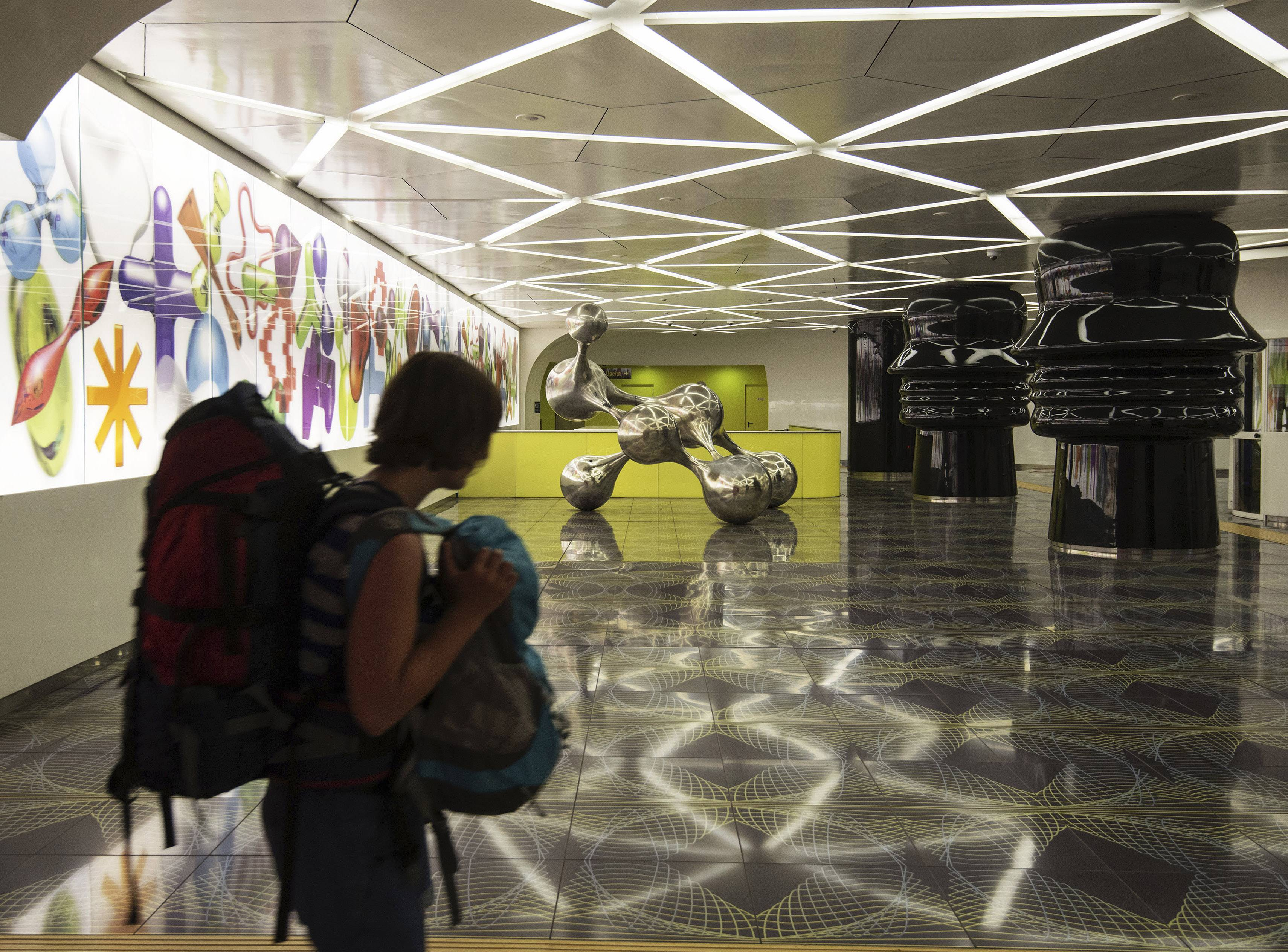 A woman walks past sculptures by Egyptian architect Karim Rashid on display in the underground metro station of Universita', part of a project called Art Stations, in Naples, Italy.