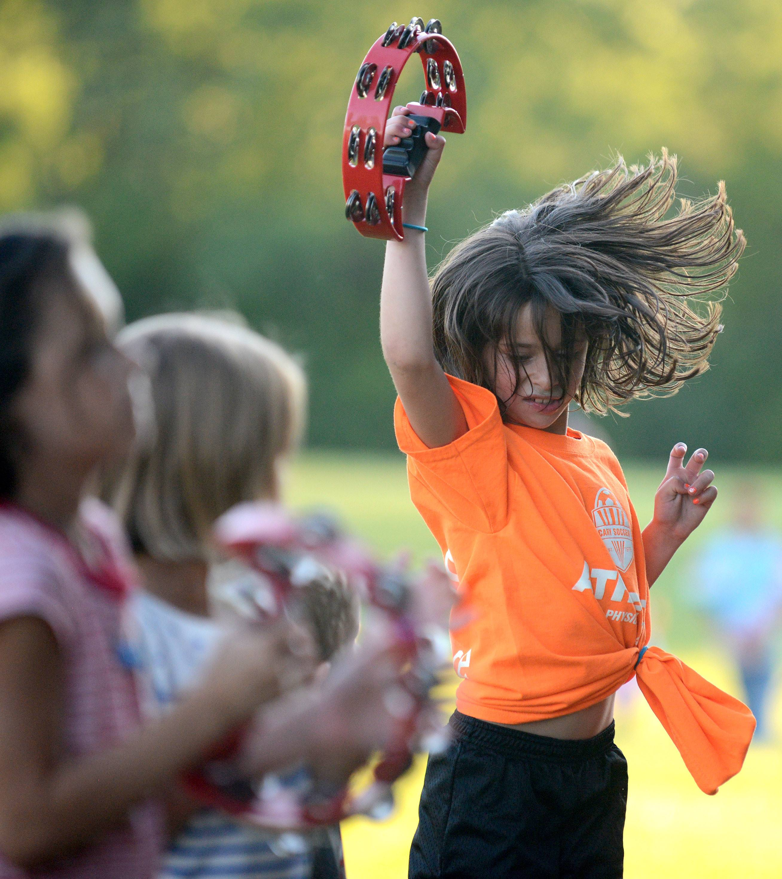 Meredith Levine, 7, of Cary rocks out to what she says is her favorite musical group, Alex and The Allstars, during the Cary Summer Celebration Thursday at Lions Park. The band brought several tambourines so kids could play along with them.