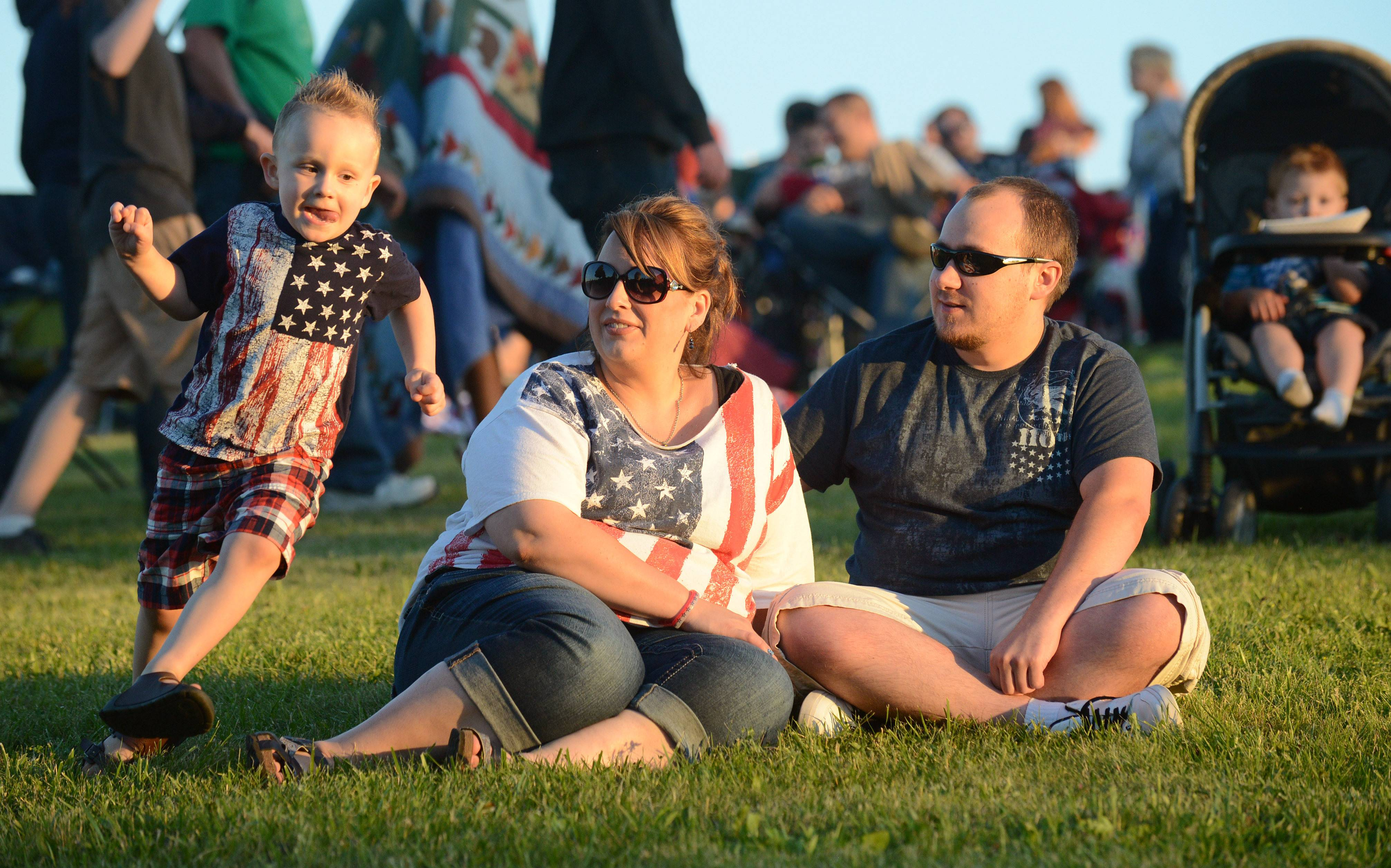 William Wendt, 3, of Island Lake runs circles around his mother, Amanda Wendt, and her boyfriend, Bryan McCaffrey of Crystal Lake, while they listen to the Alex and The Allstars at the Cary Summer Celebration Thursday at Lions Park on Thursday. The trio planned to stick around for the fireworks show, too.