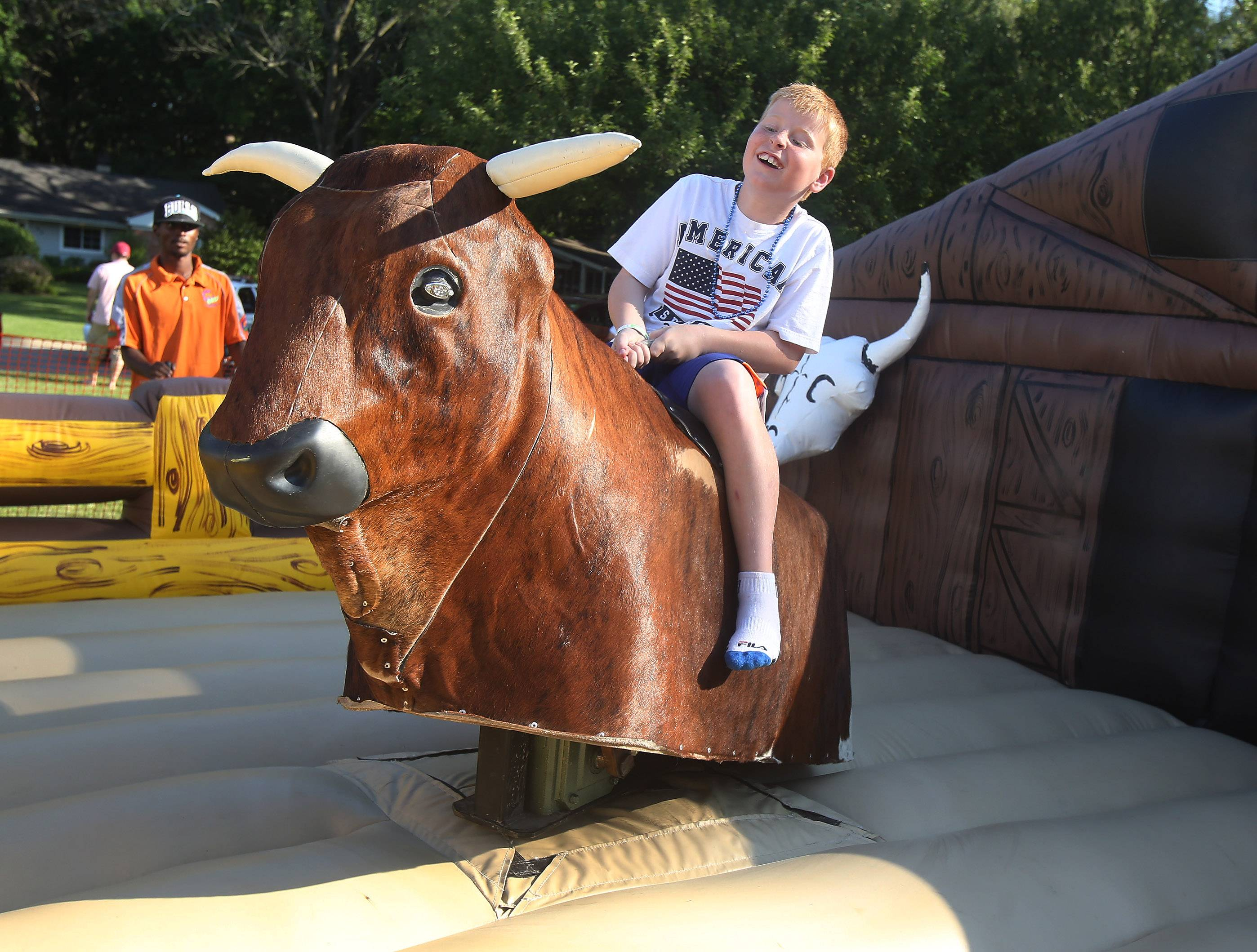 Conrad Dick, 10, rides the mechanical bull during the first day of Lincolnshire's Red, White & Boom celebration Thursday at Spring Lake Park. The Lincolnshire Community Association festival featured a mechanical bull riding competition, vintage car show, games, food and entertainment.