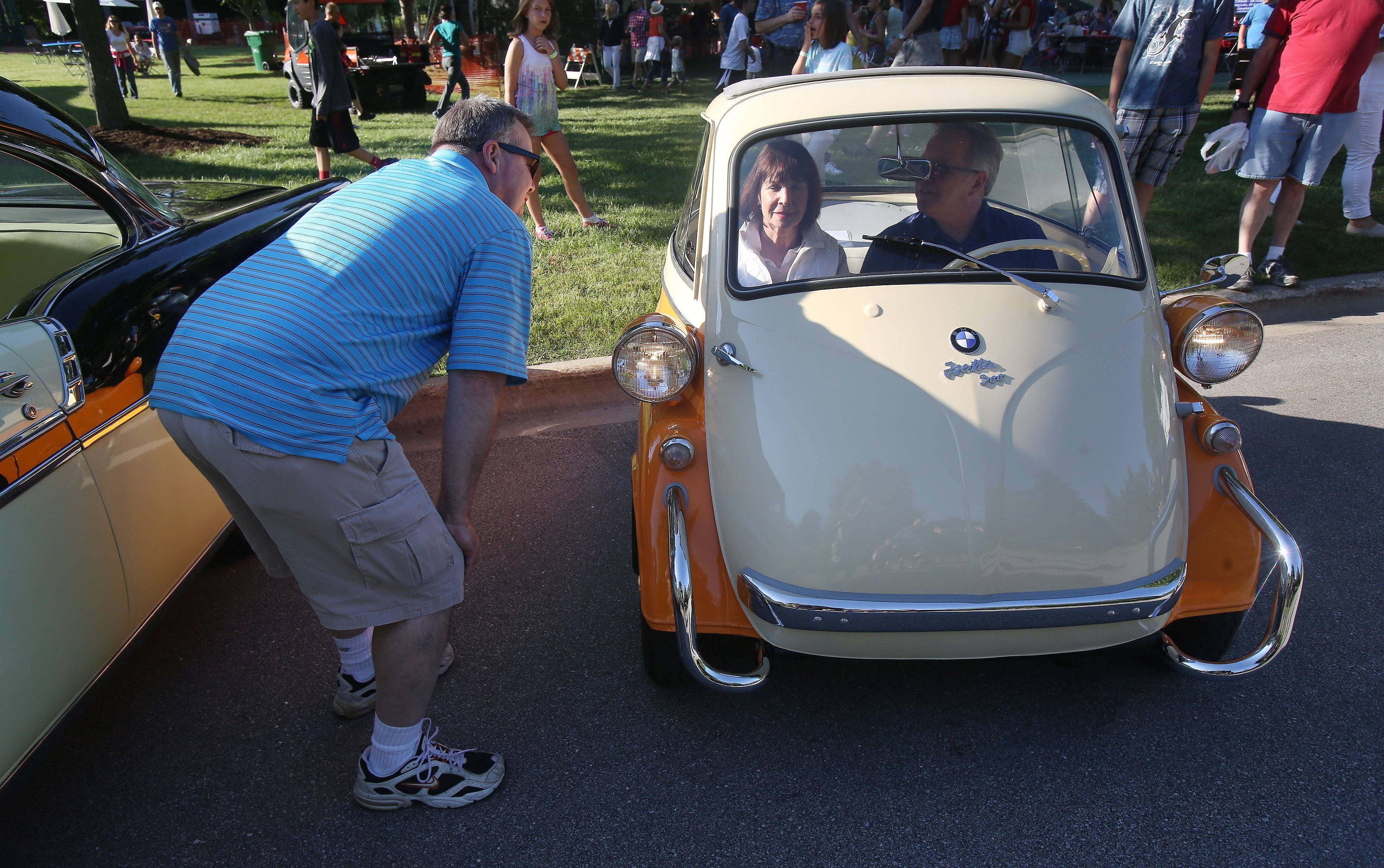 Mike Denning, left, talks to Ron and Claudia Markoya after they arrive in a BMW Isetta 300 to the classic car show during the first day of Lincolnshire's Red, White & Boom celebration Thursday at Spring Lake Park.